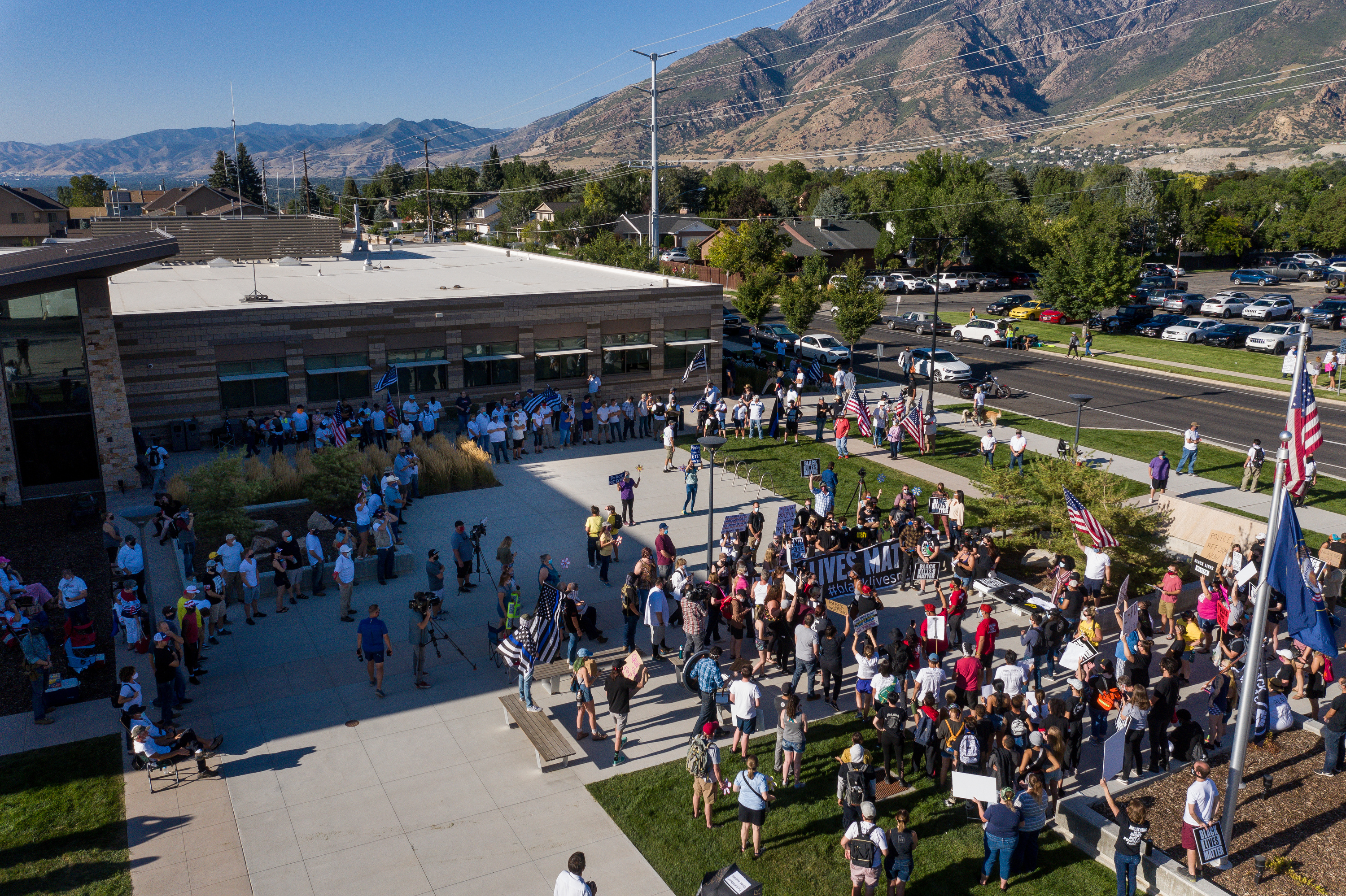 Black Lives Matter Utah holds a protest while counterprotesters, left, watch outside the Cottonwood Heights police department on Friday, Aug. 7, 2020.