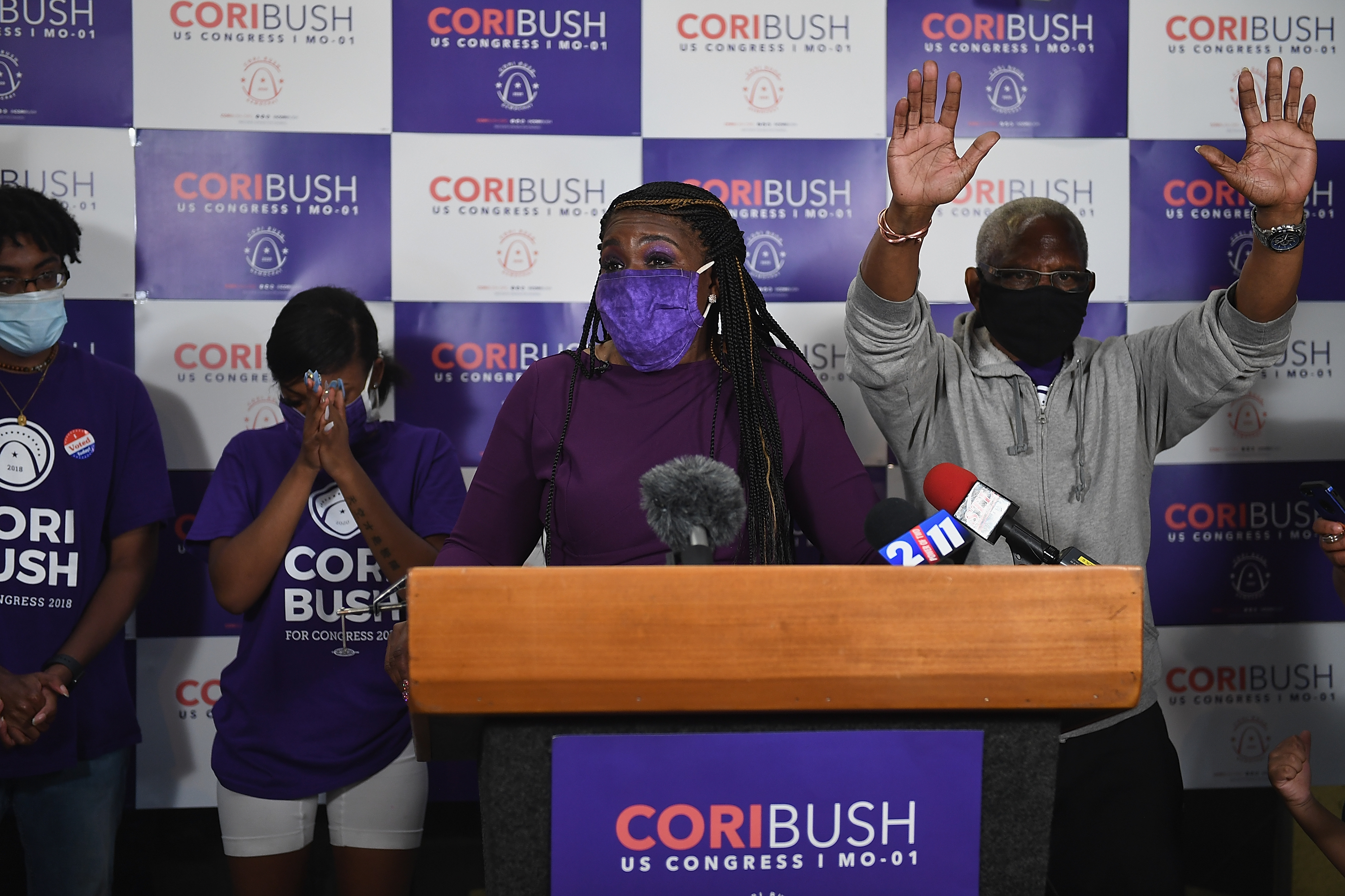 Congressional candidate Cori Bush wears a mask while giving a speech from behind a podium. Campaign supporters stand behind and to the sides.