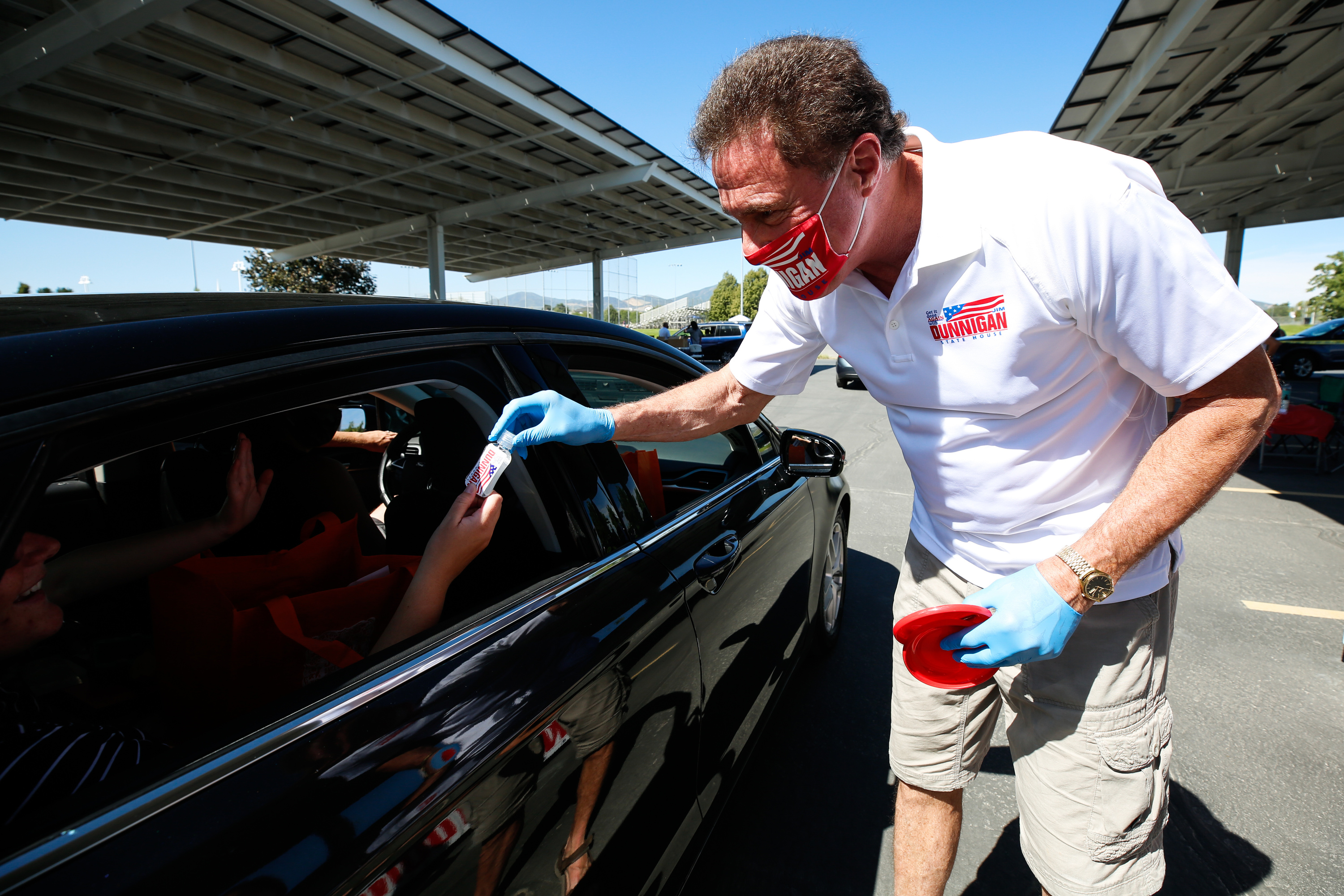 Rep. Jim Dunnigan gives out hand sanitizers to participants during the Hometown Day drive through event at Utah Olympic Oval Parking Lot in Kearns on Saturday, Aug. 8, 2020.