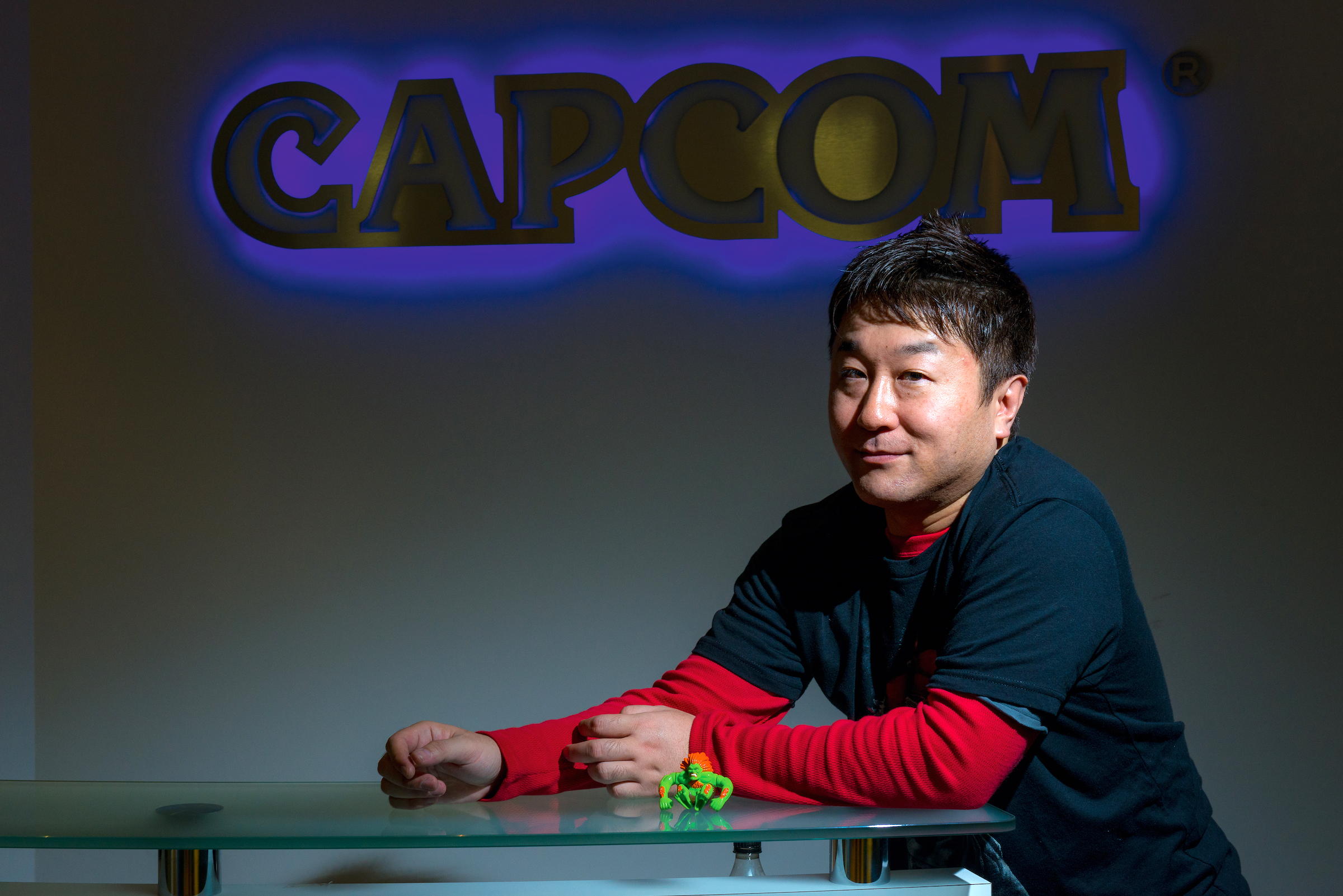 Ex-Capcom producer and brand manager Yoshinori Ono sits at a table with a Blanka figure, with the Capcom logo behind him
