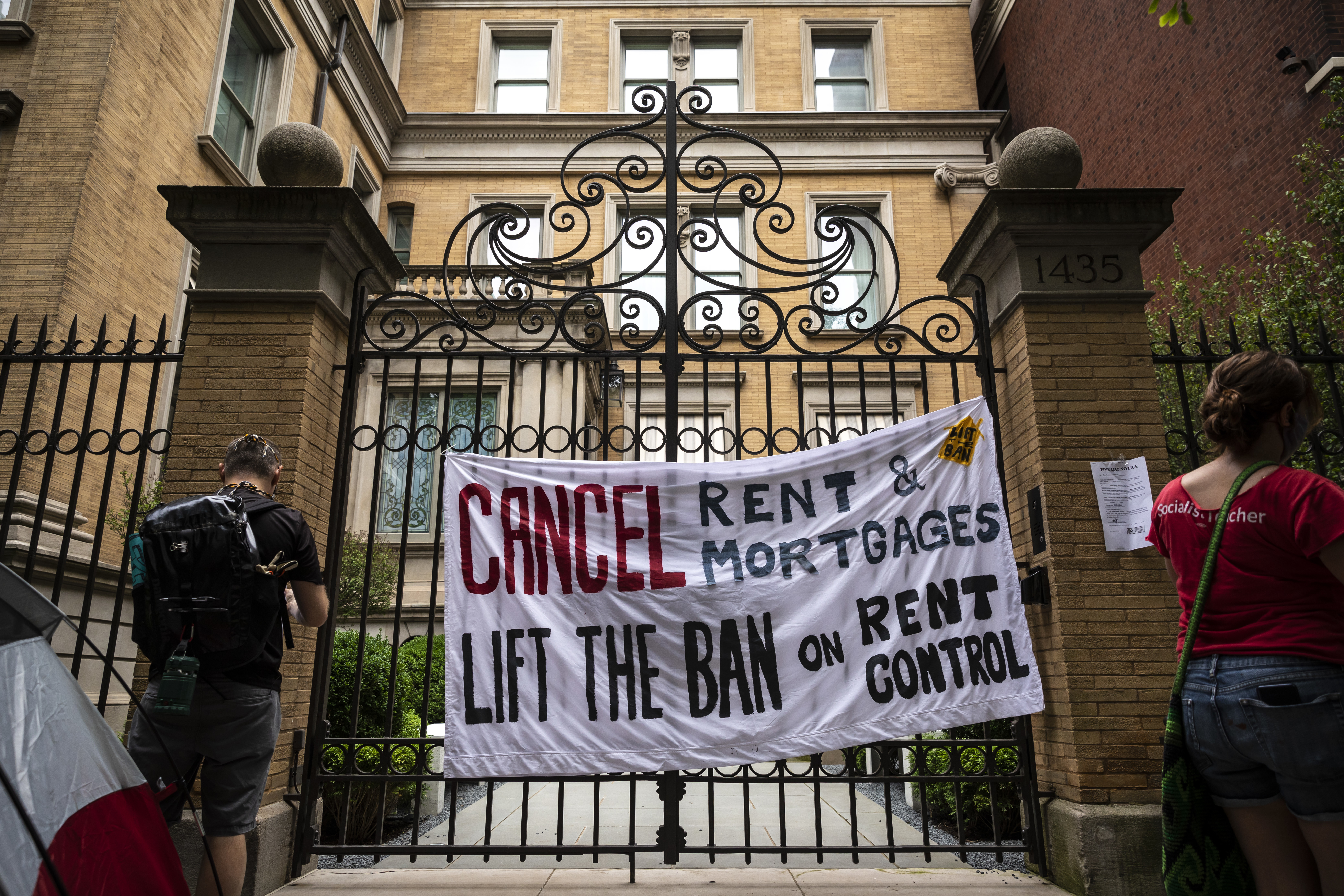 "Protesters calling for Gov. J.B. Prtizker to lift the ban on rent control in Illinois during the coronavirus pandemic hang a sign and post ""eviction notices"" on the governor's Gold Coast mansion on North Astor Street, Tuesday afternoon, June 30, 2020."