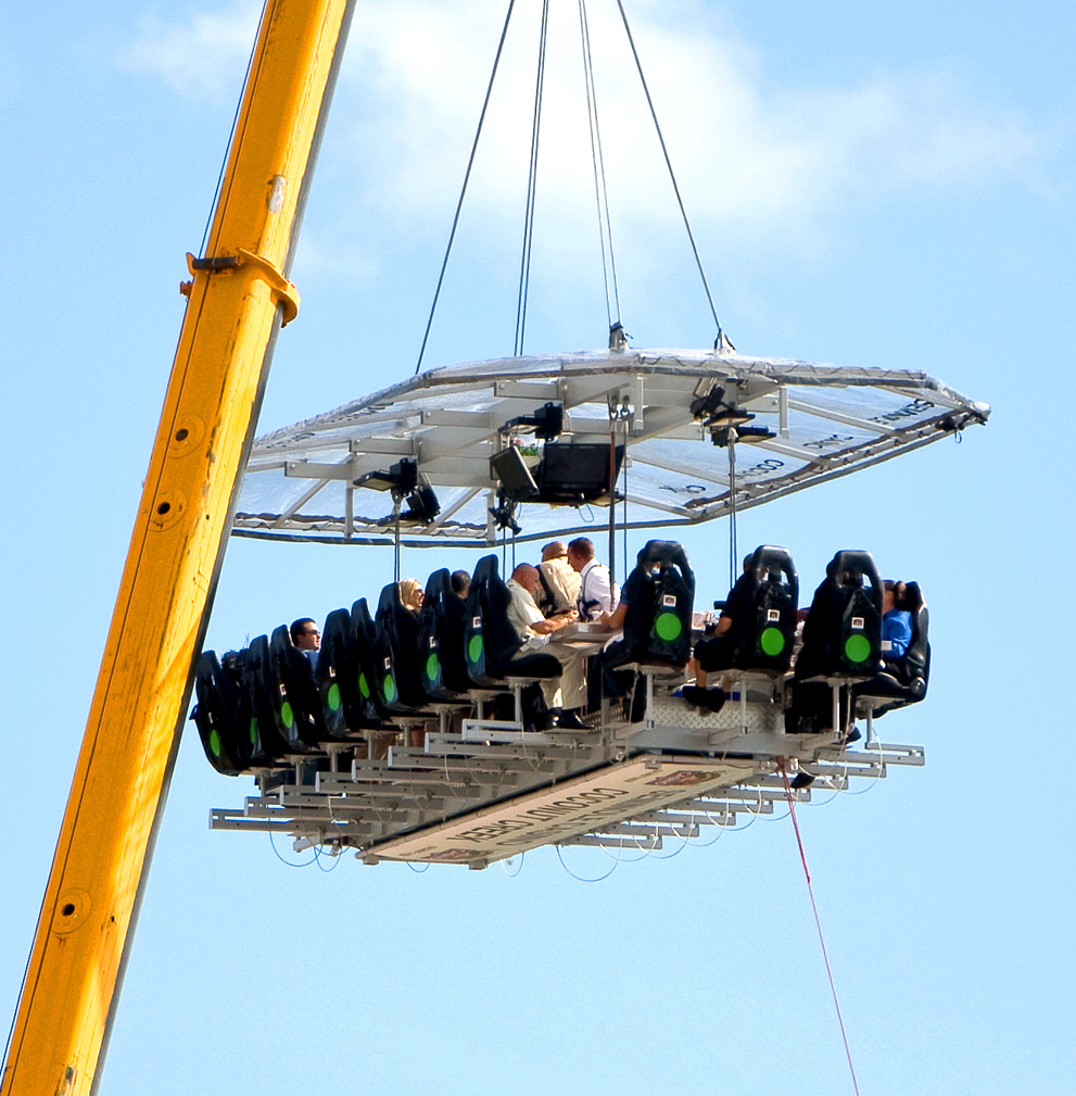 A dinner party is suspended up in the sky by a crane, with diners in amusement park ride-like seats