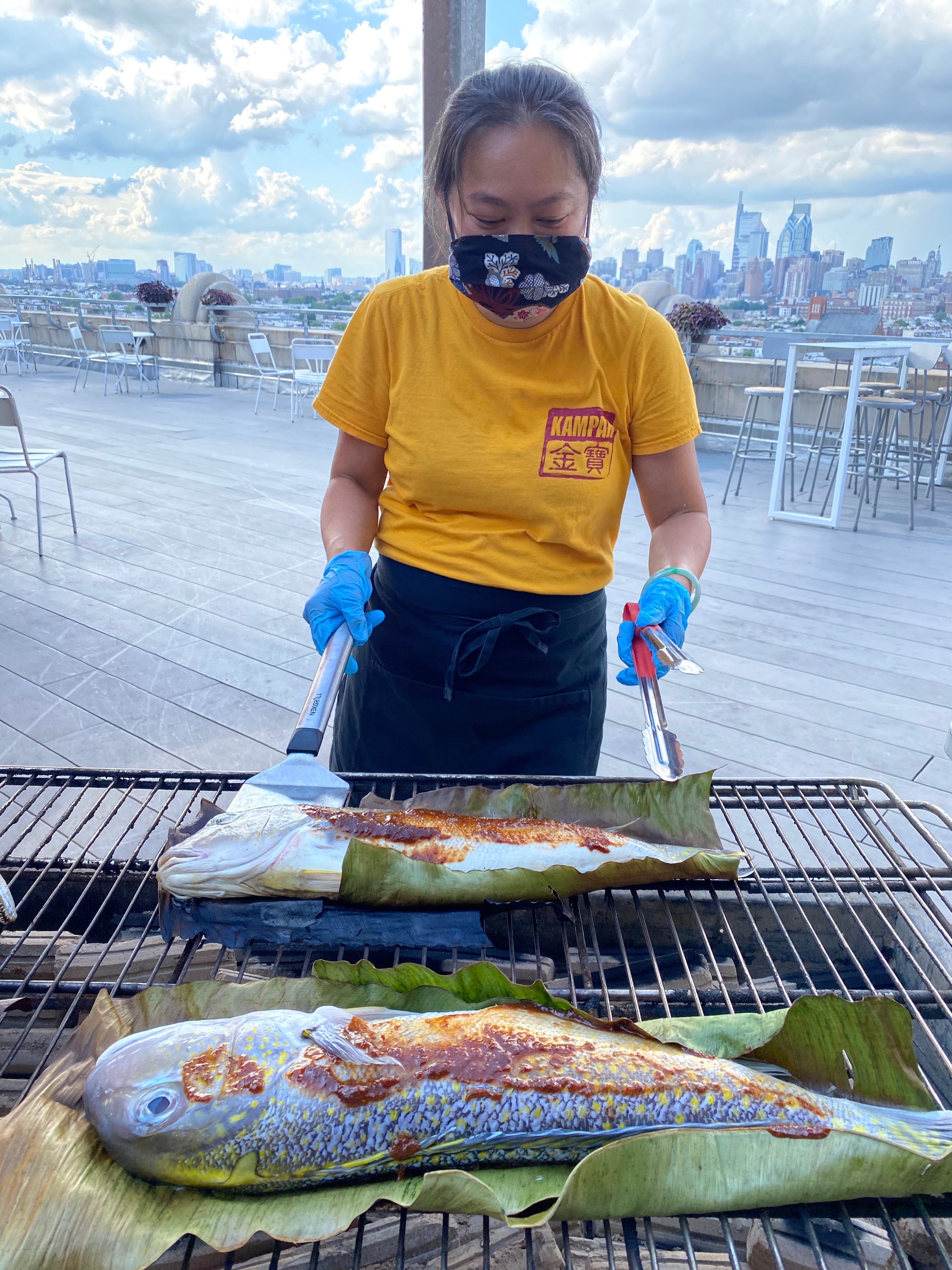 woman in yellow shirt standing at a grill cooking whole fish