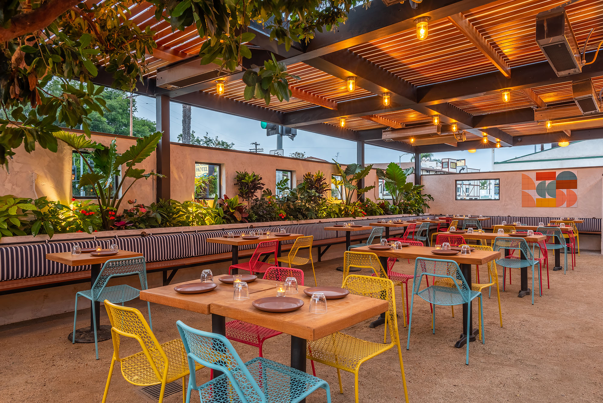 Nueva Venice's colorful covered outdoor patio in Venice, California with yellow and blue chairs.