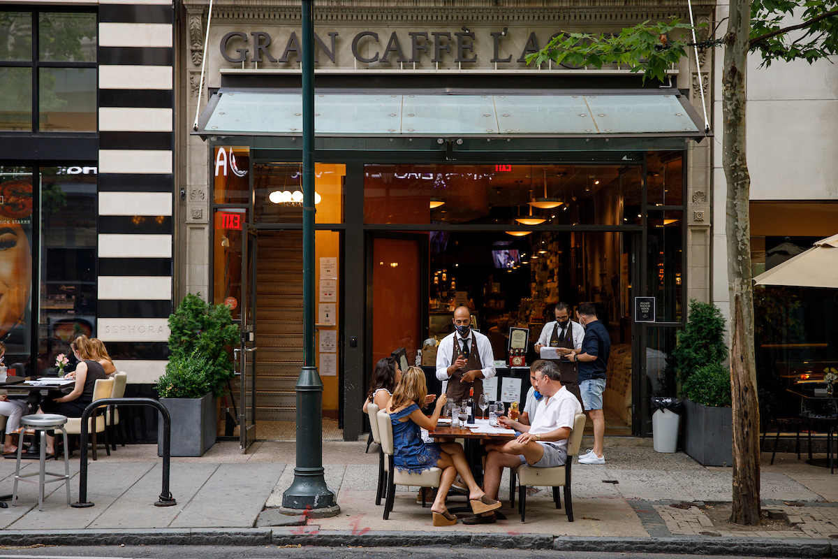 people dining at sidewalk table in front of restaurant with server wearing a pandemic face mask