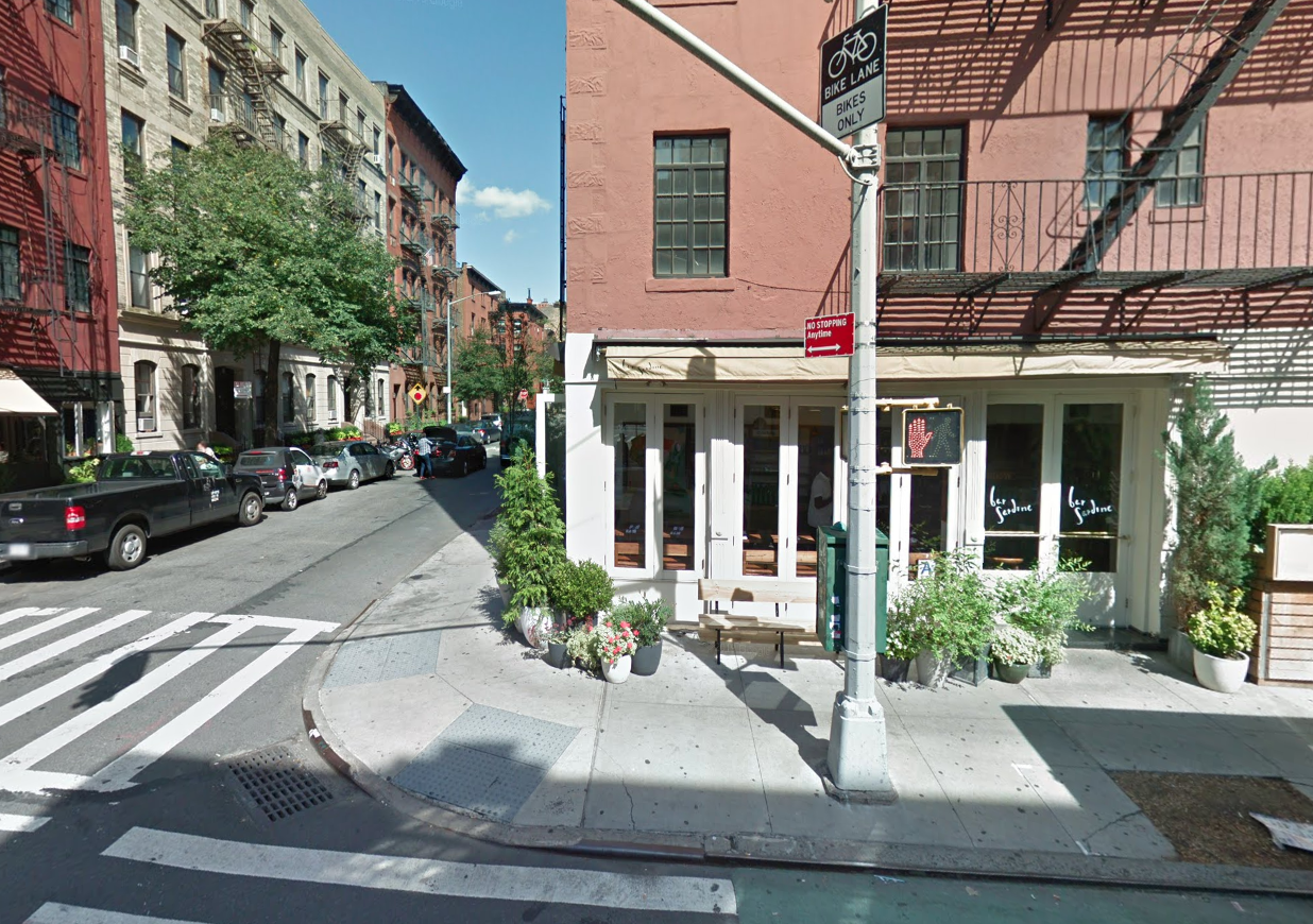 A sunny, white restaurant facade on a corner of two streets