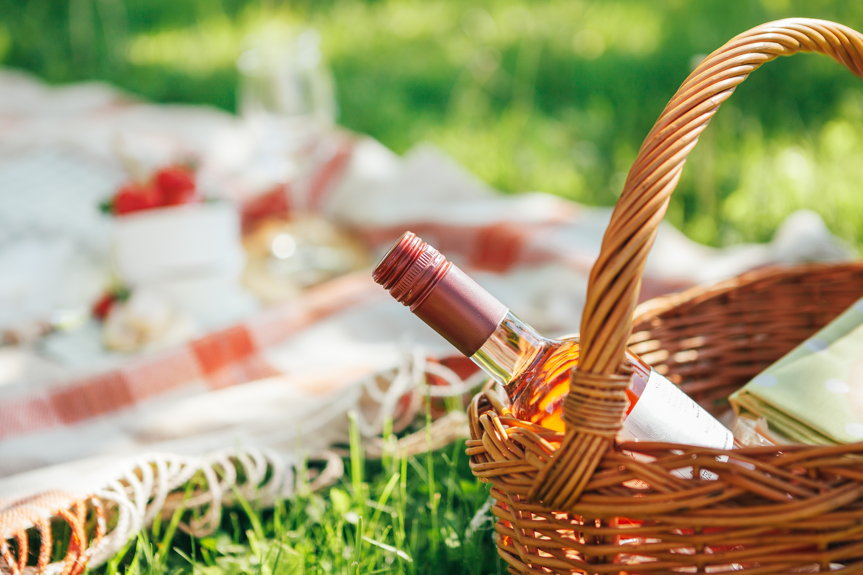 A picnic basket with bottle of rose wine and a checked blanket on the grass with food in the background