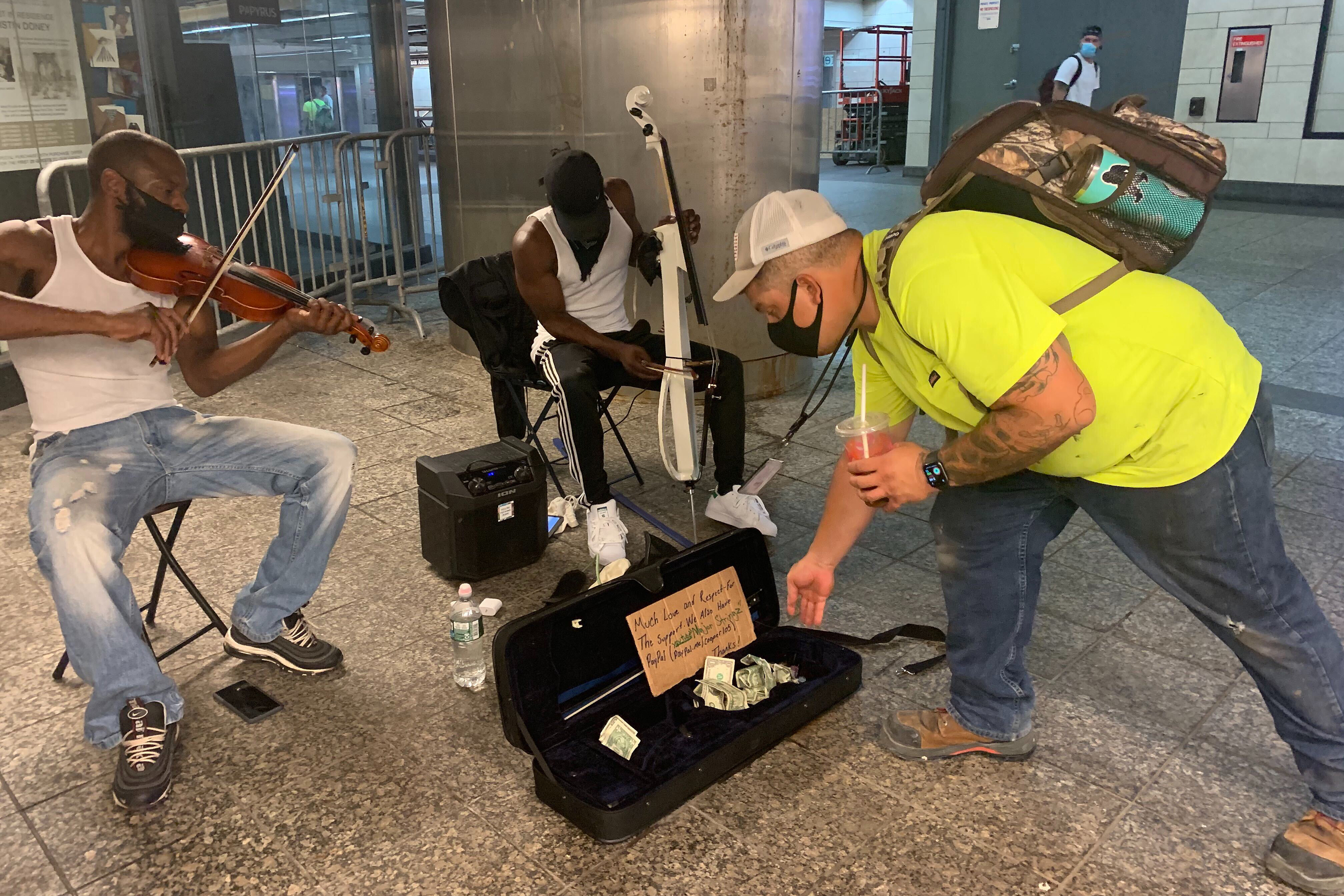 Subway musicians Lamont Stokes, right, and his brother, Antwon, perform near the turnstiles at 34th Street-Penn Station, Aug. 10, 2020.