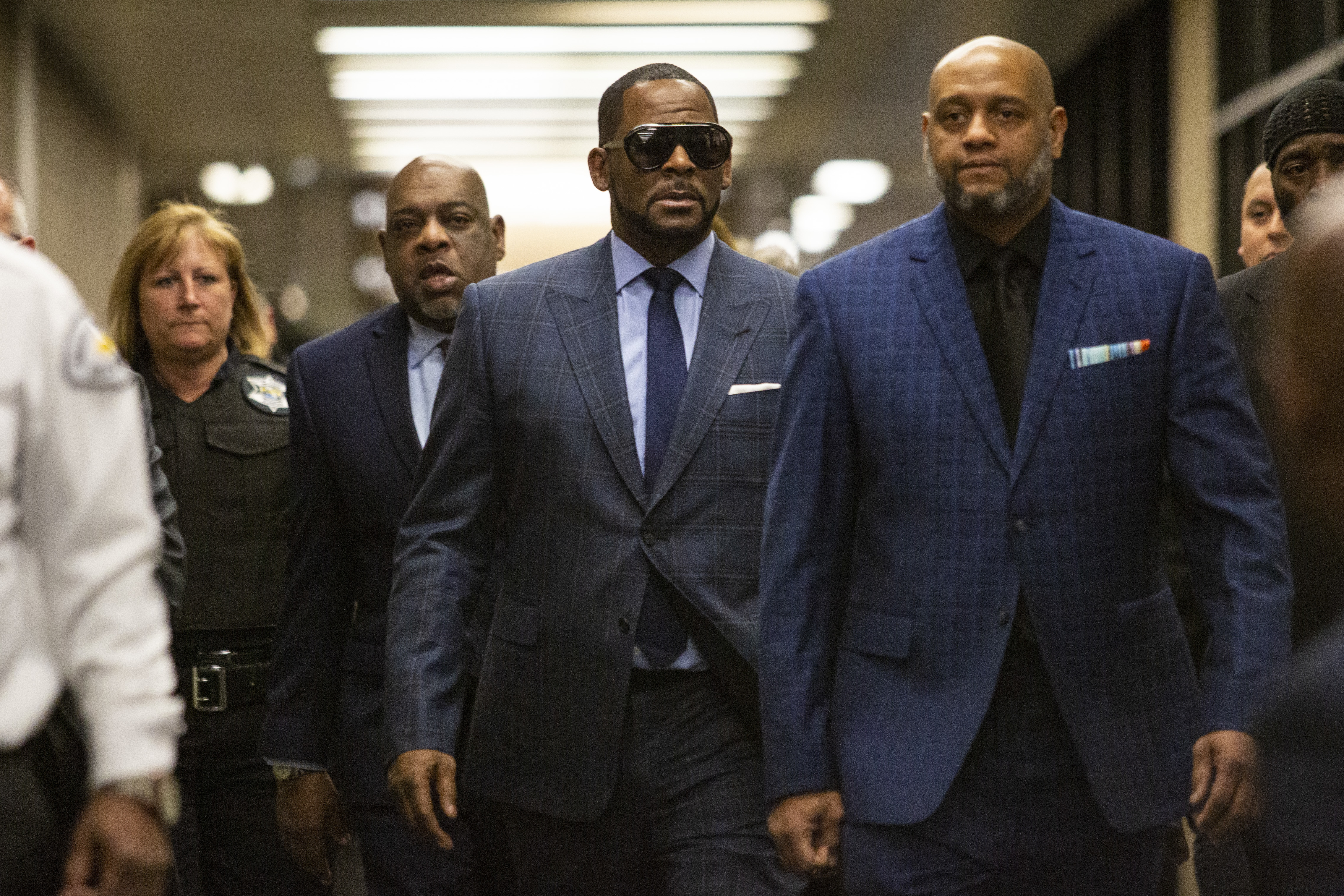 R. Kelly walks with supporters into the Daley Center in Chicago for a hearing in a child support case in March 2019.