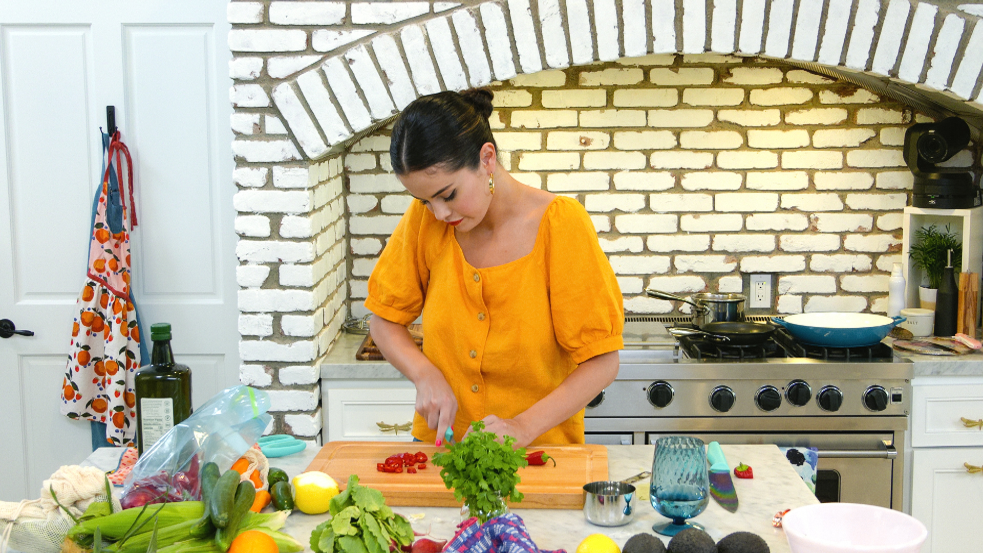 Selena Gomez chopping a pepper in her home kitchen.