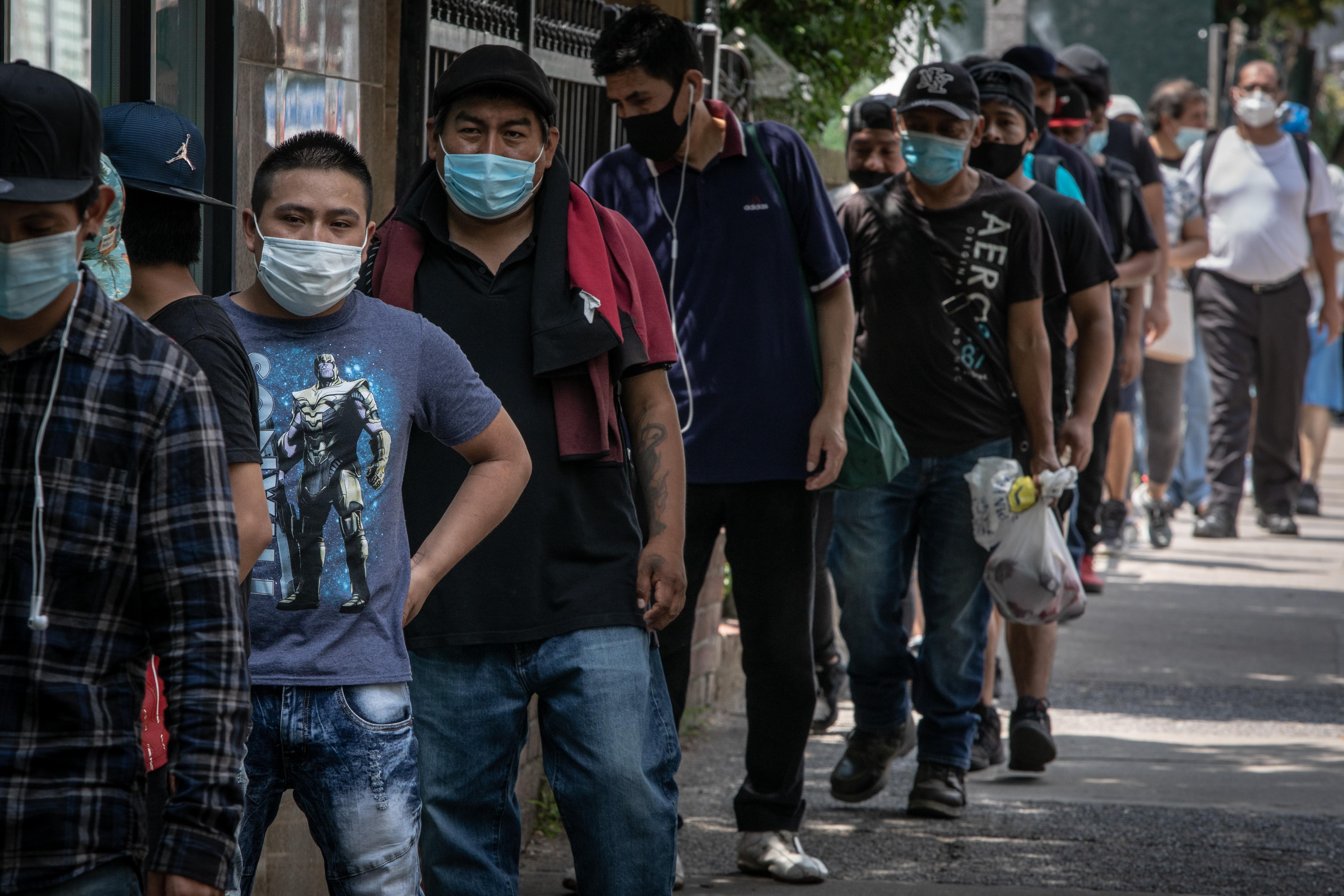 Men in masks waiting in line