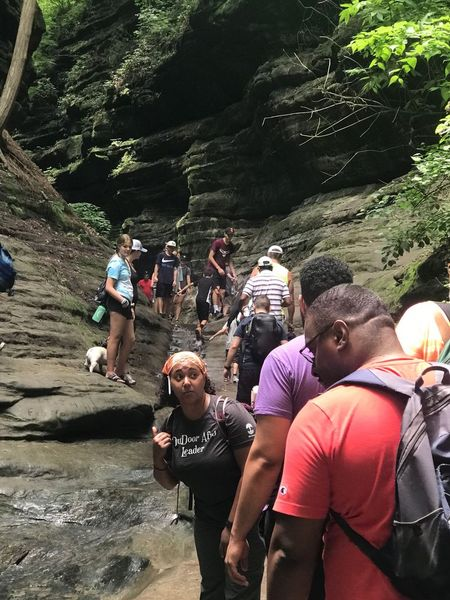 A group of around ten hikers climb up into a canyon
