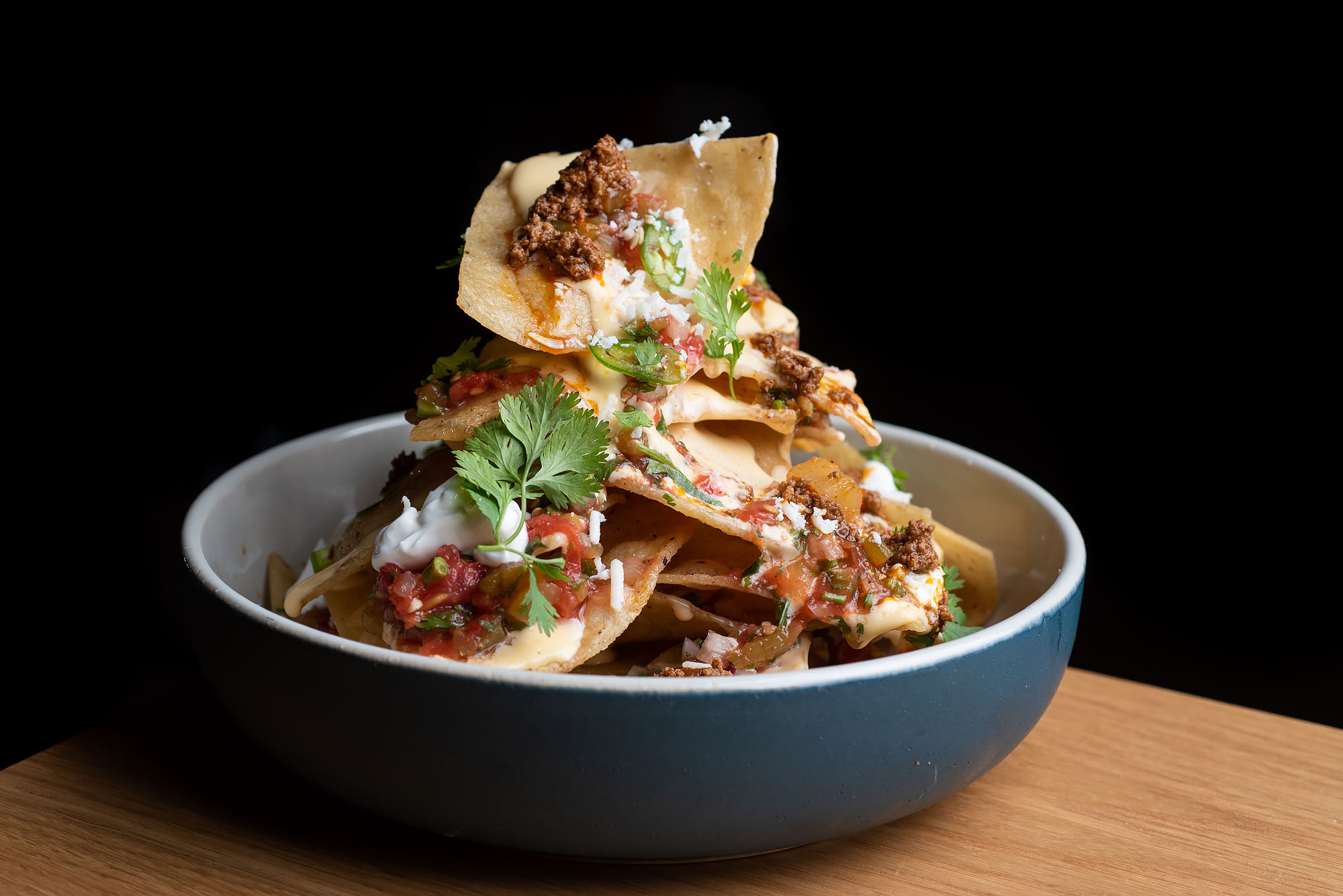 Stack of nachos with meat, cheese, and condiments at Amacita restaurant in Culver City on a wood table and a dark background.