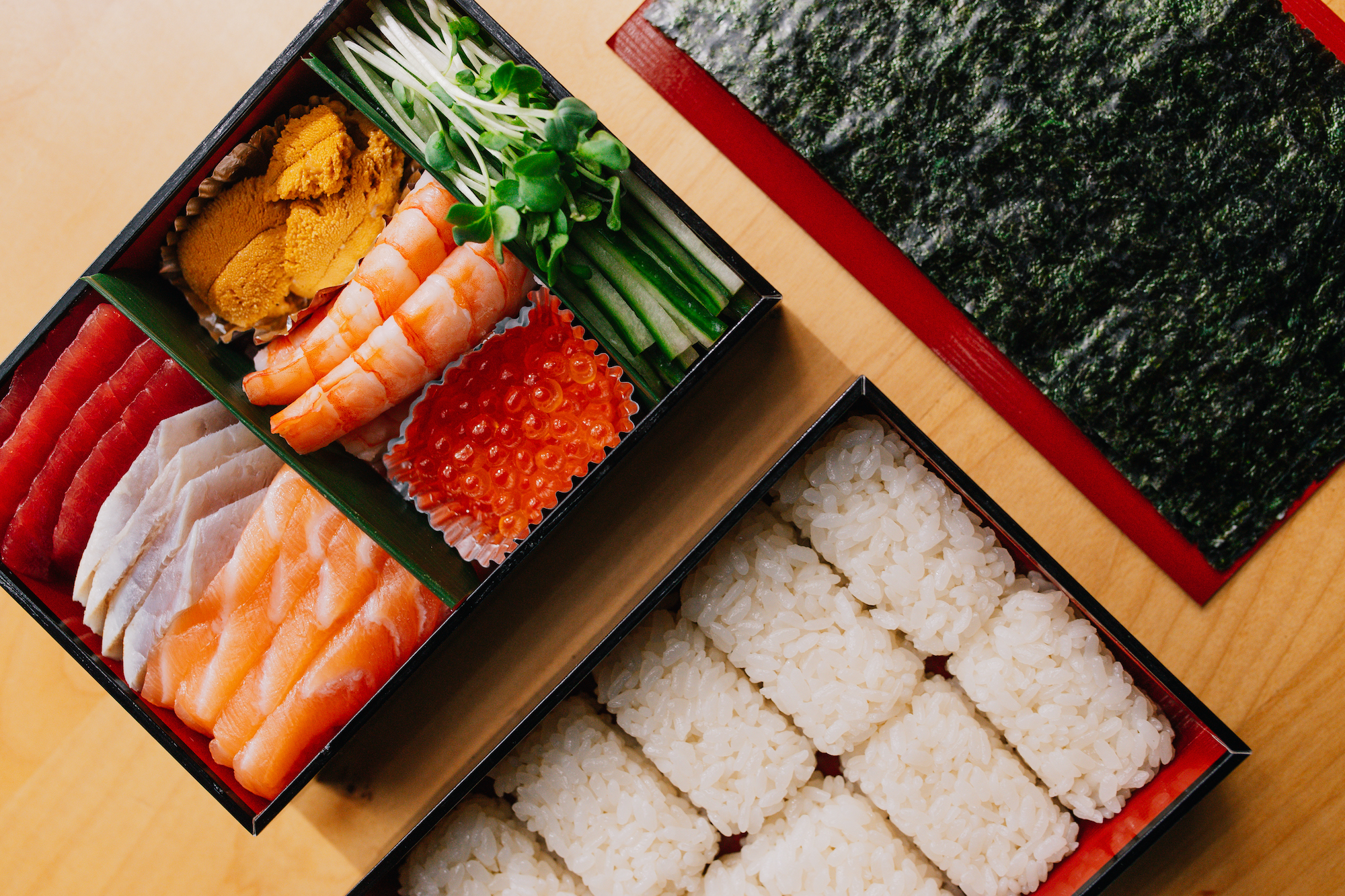 From above, a shot of sushi takeout in a box, with nori and rice on the side.