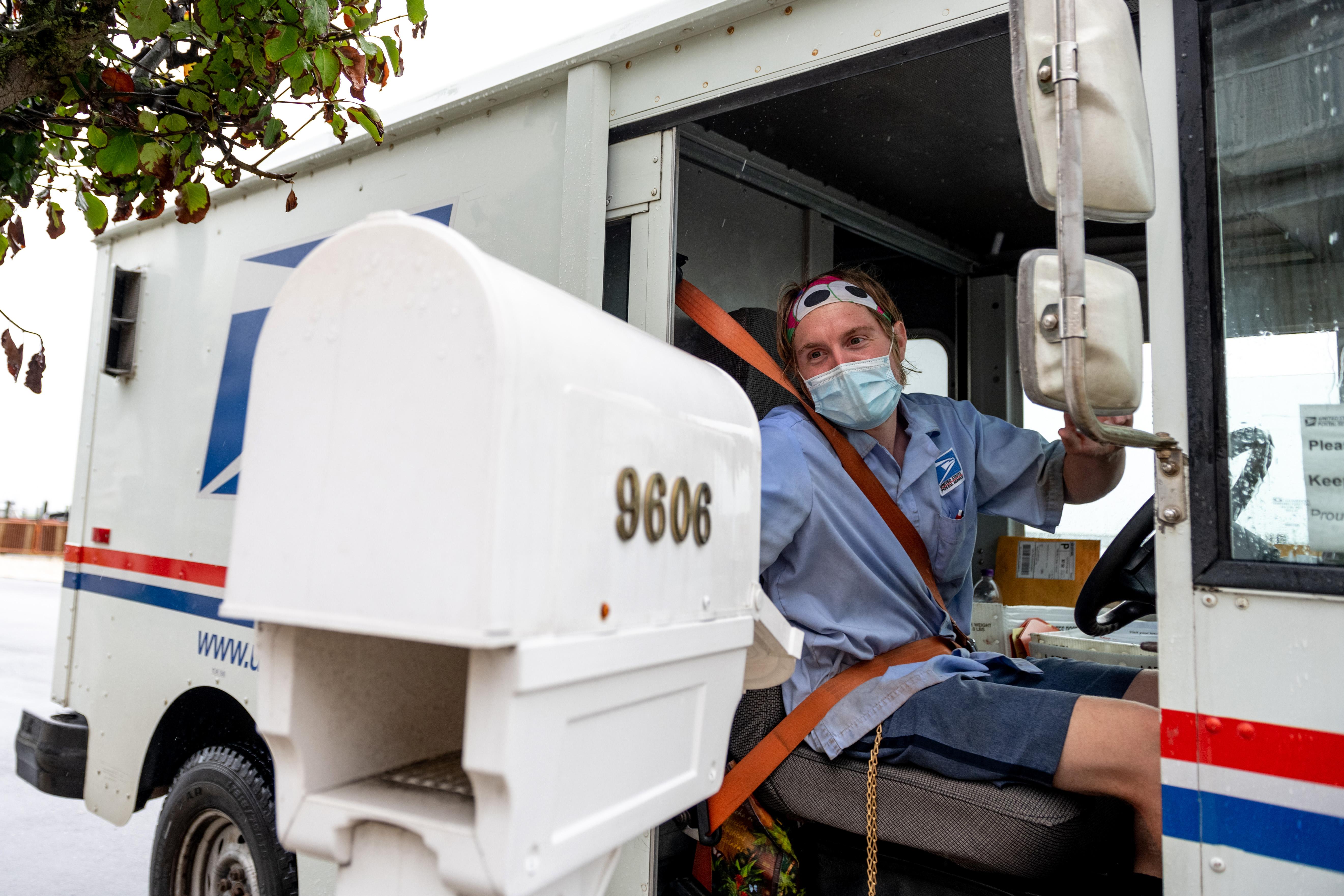 Postal worker in mask delivering mail