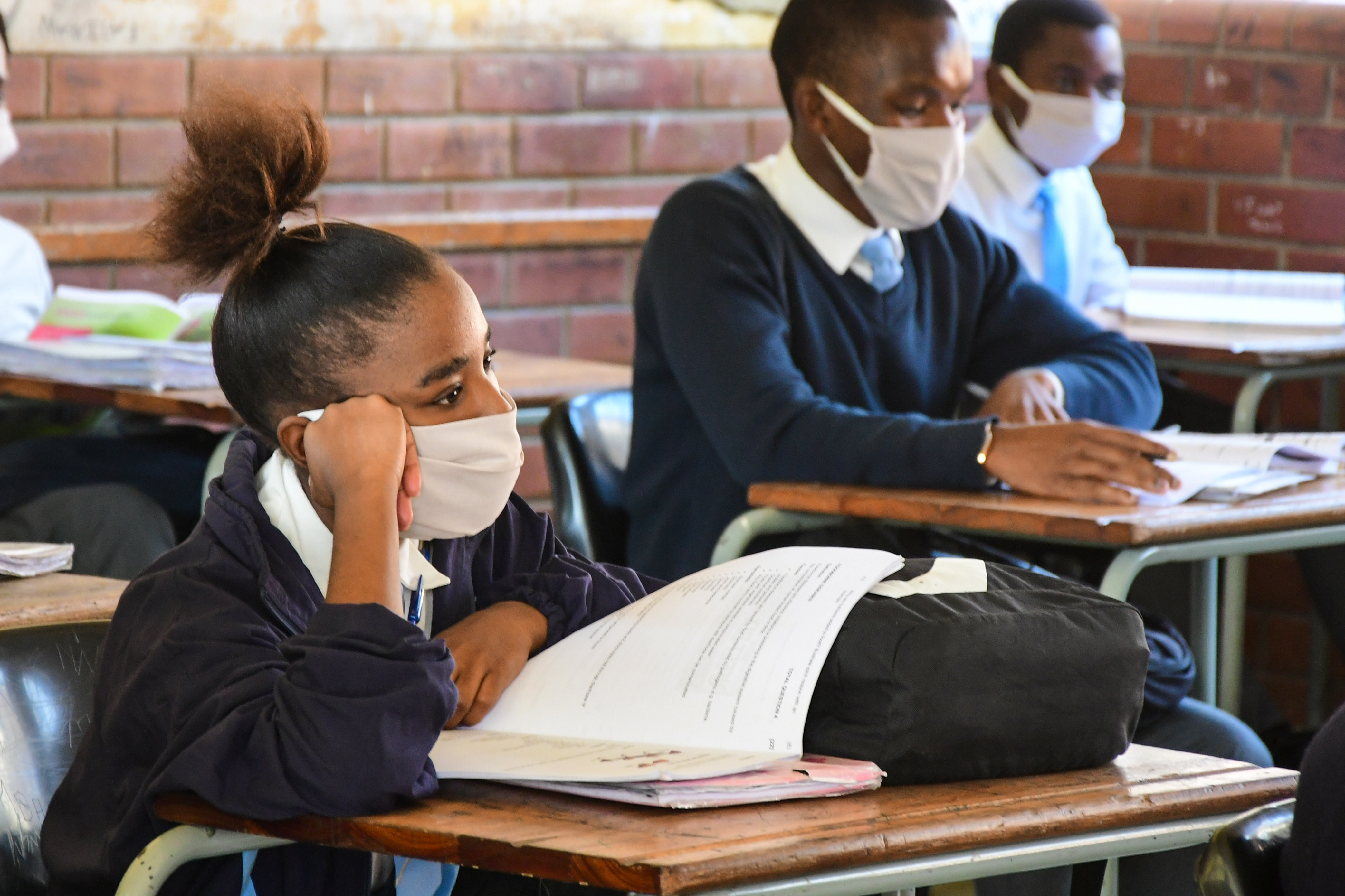 A student in a face mask sitting at a school desk with her head propped on her fist, Durban, South Africa, June 9, 2020.