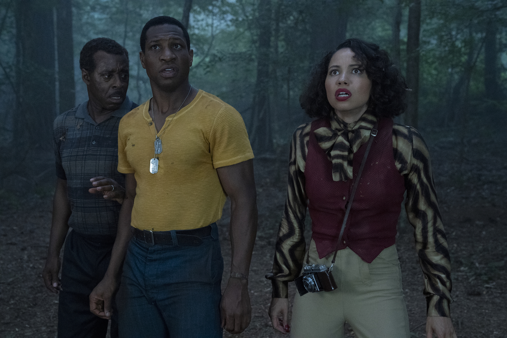 Lovecraft Country's Courtney B. Vance, Jonathan Majors, and Jurnee Smollett stand in a forest at night, looking with concern at something offscreen.
