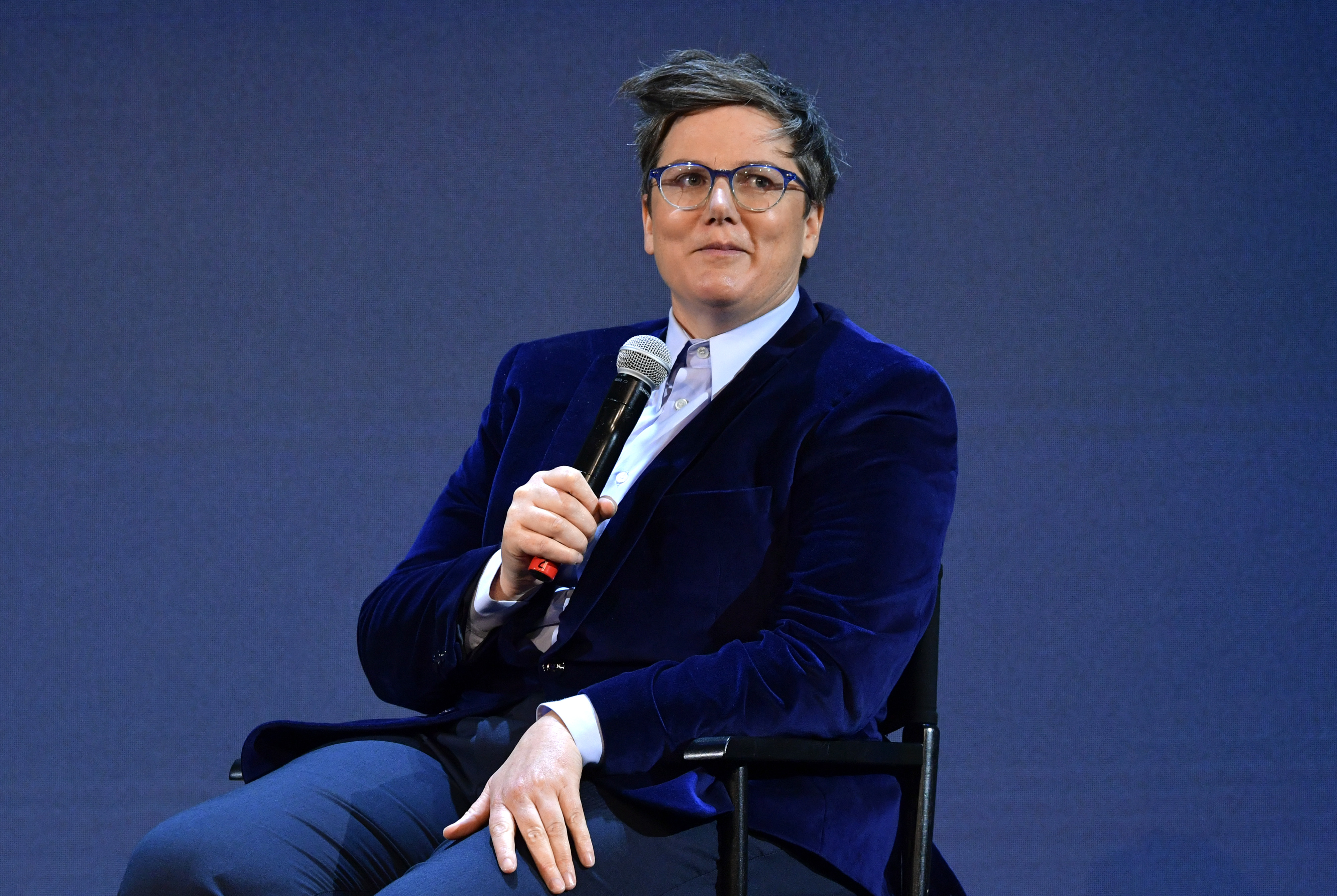 Comedian Hannah Gadsby sitting onstage holding a microphone.