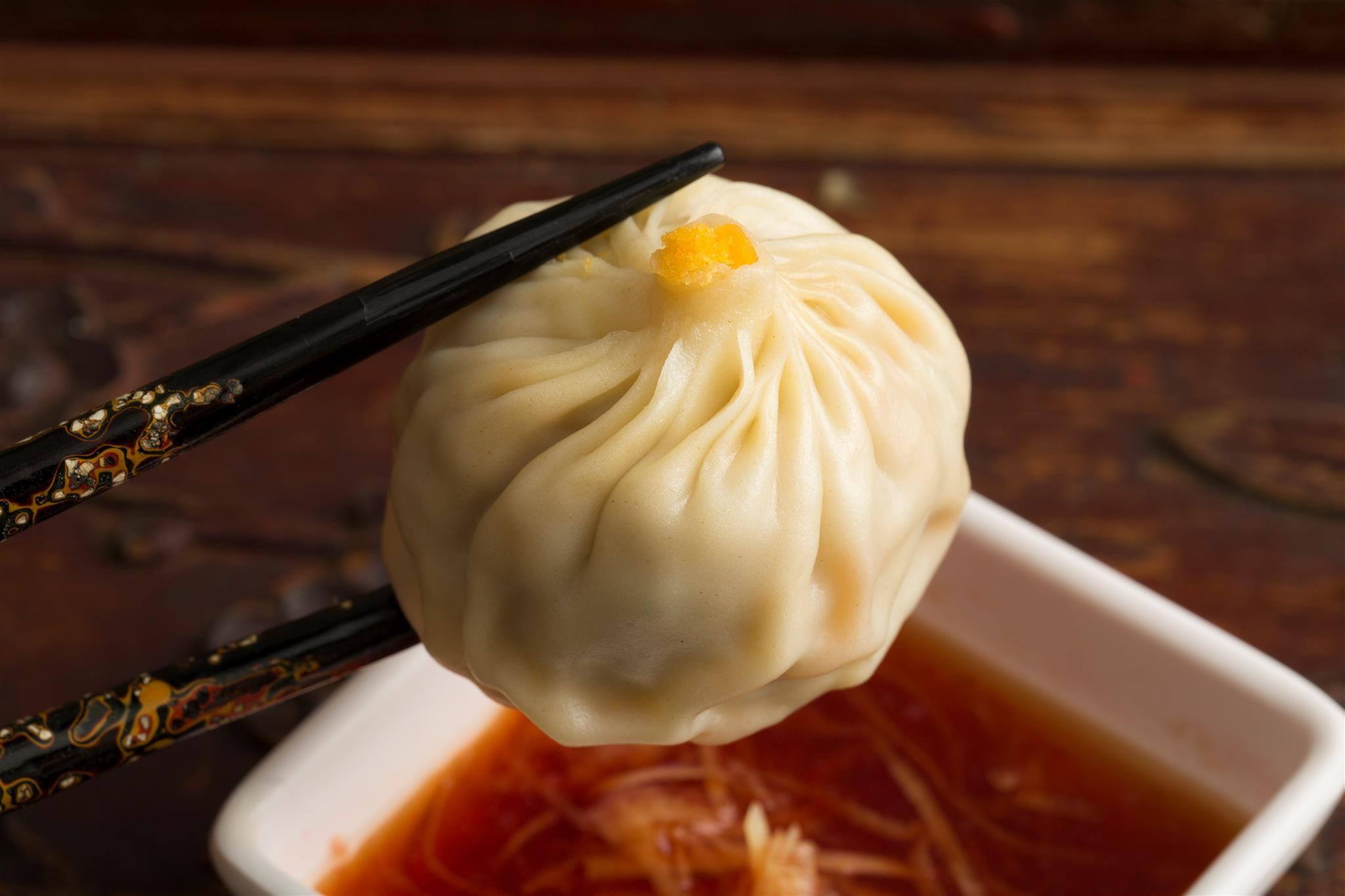 A dumpling held by chopsticks