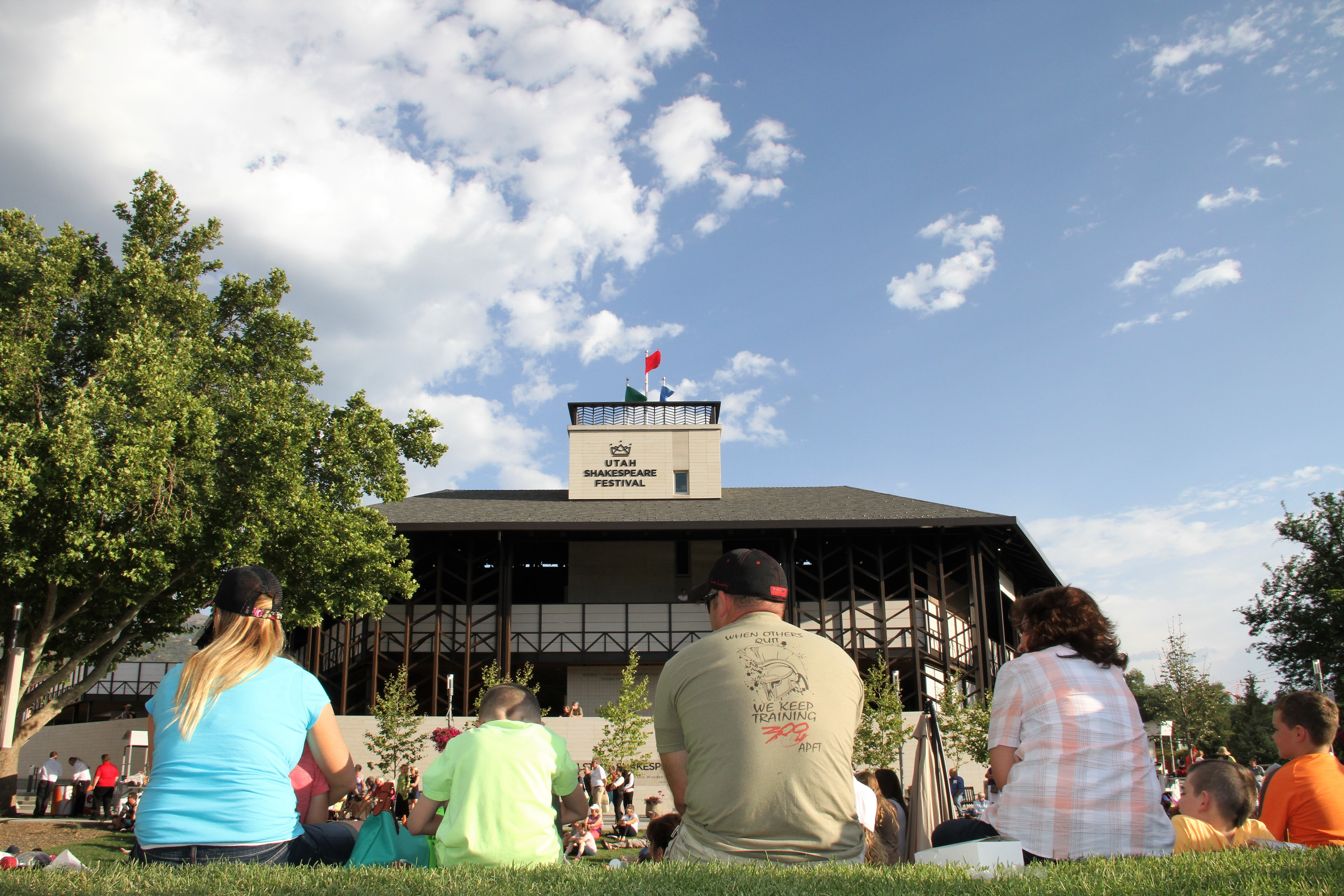 People lounging on the grass at the Greenshow at the 2017 Utah Shakespeare Festival, with the Engelstad Shakespeare Theatre in the background. On Monday, the festival announced its 2021 season.