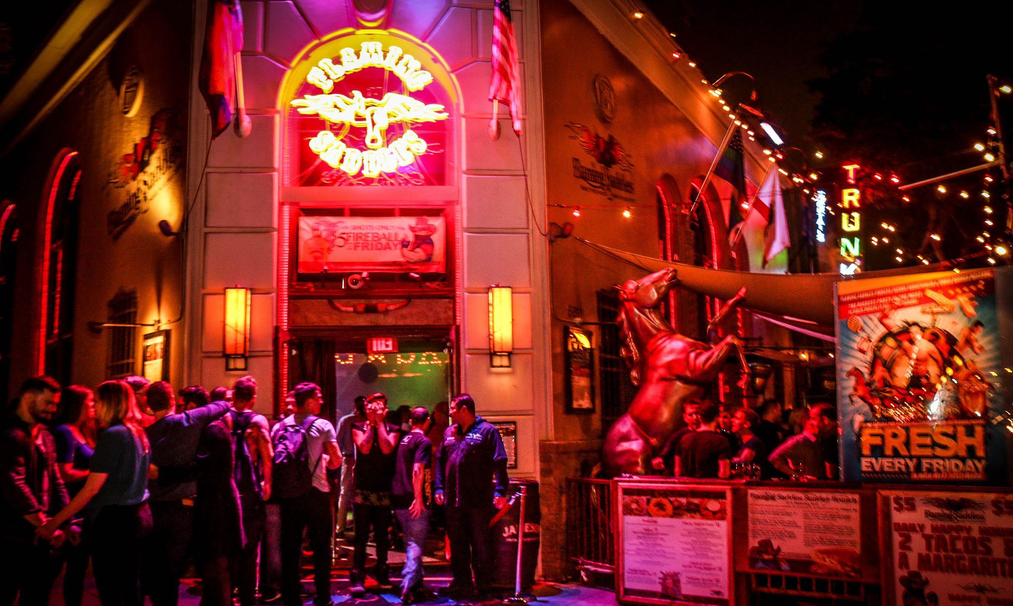 A nightlife scene in front of a neon-lit gay bar in West Hollywood, CA.