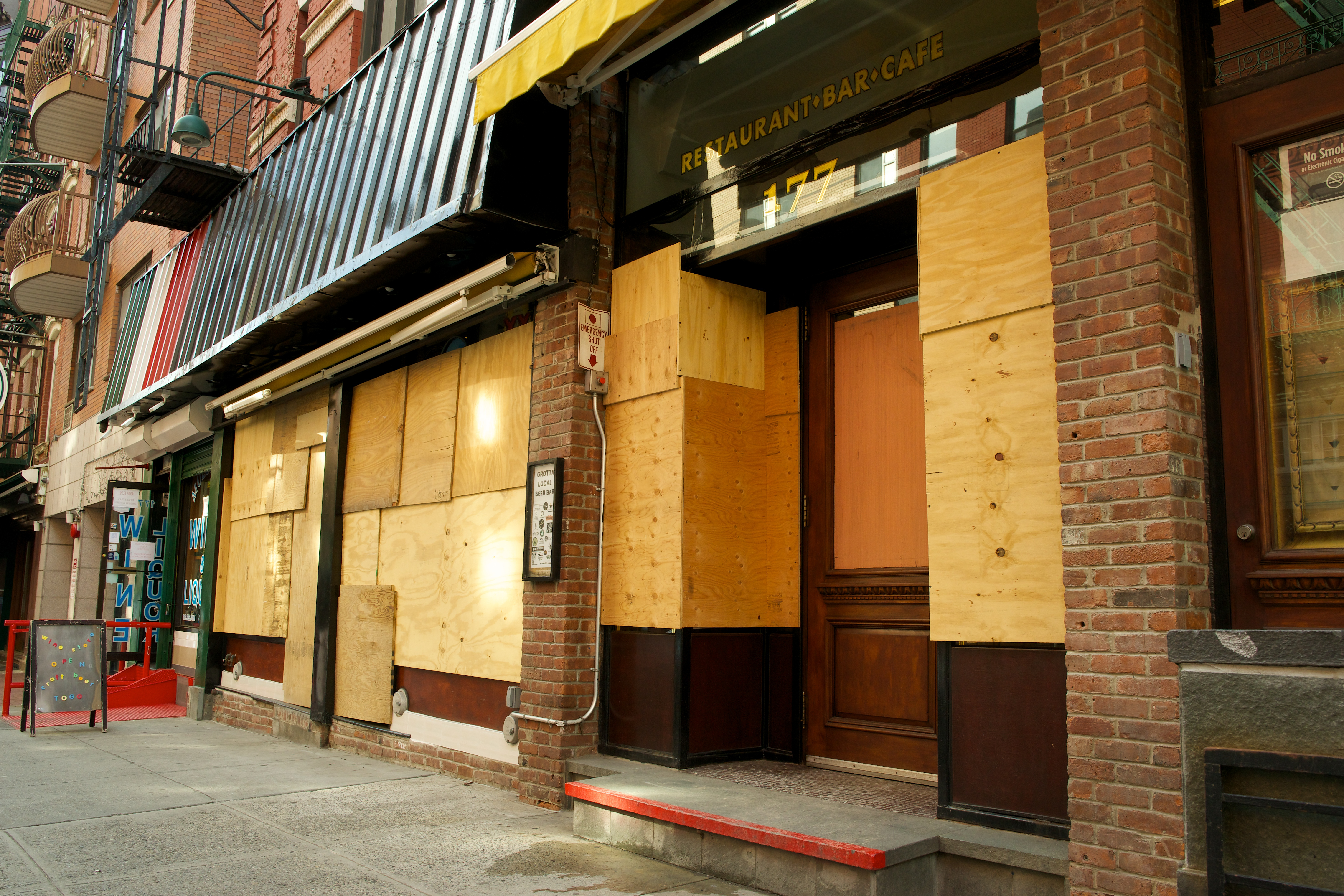 The brick exterior of a vacant New York City restaurant space, its windows boarded shut with plywood.