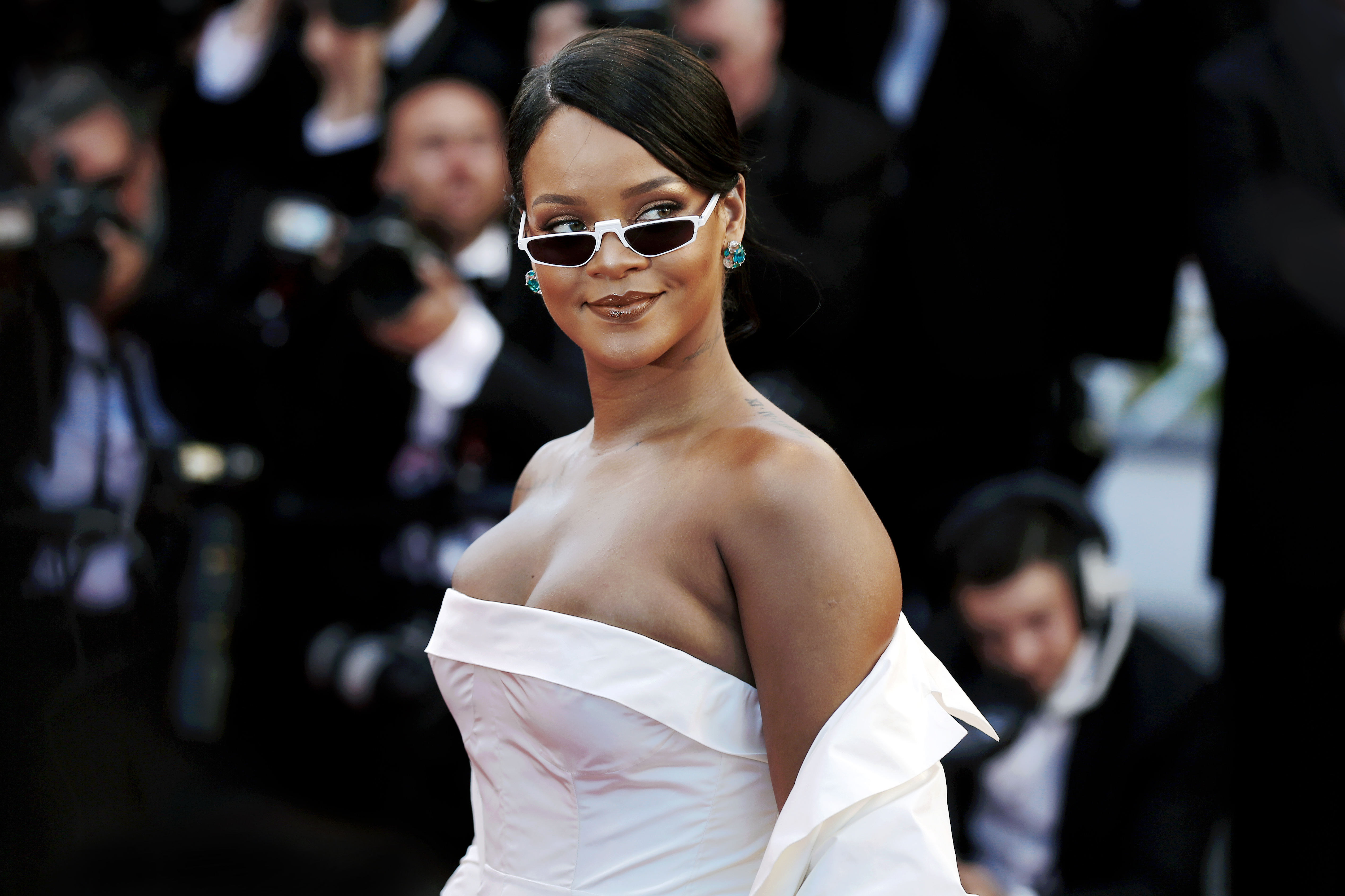 The singer Rihanna wearing a white gown and white glasses, looks toward the camera.