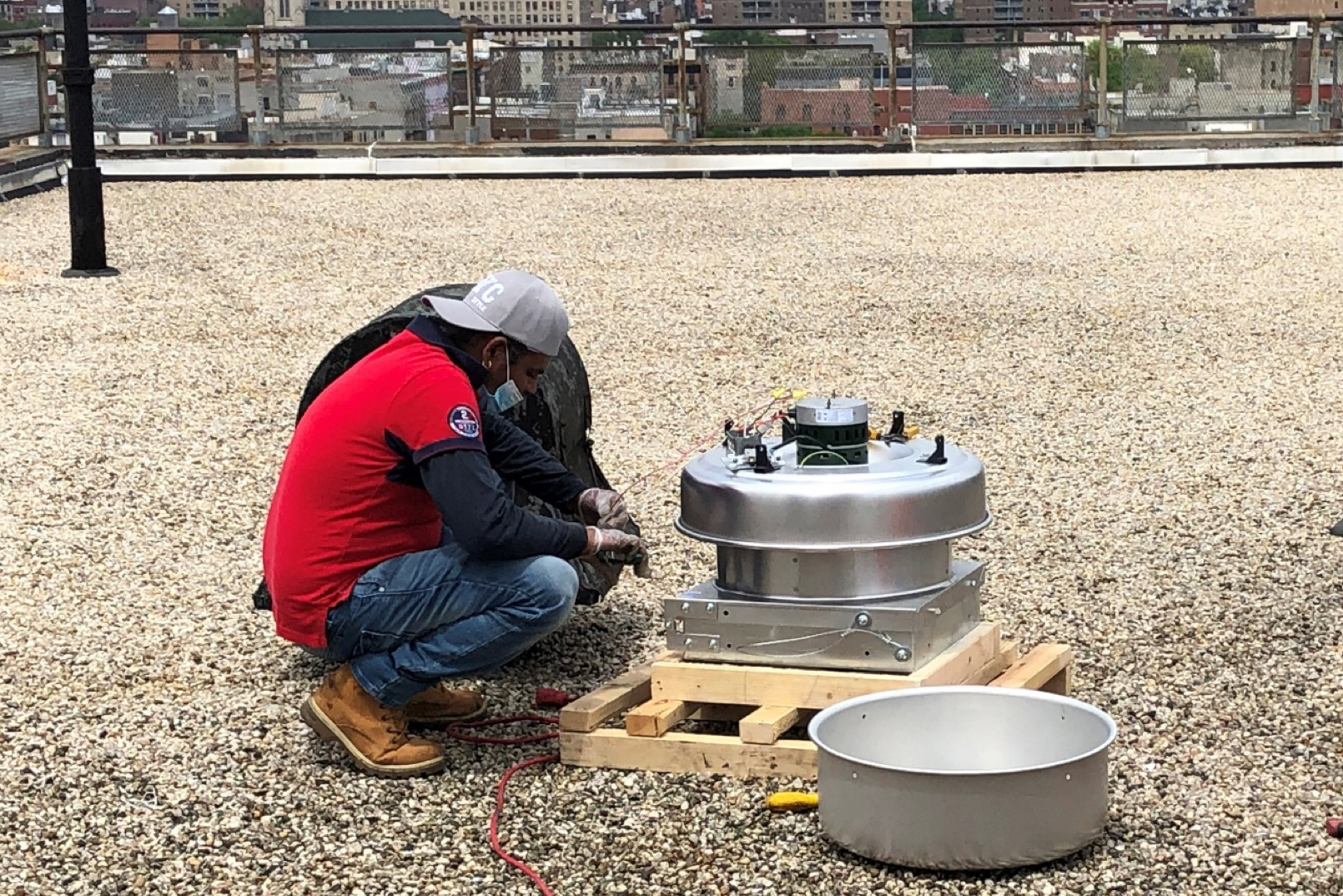 A worker installs a fan on the roof of a Wald Houses roof in the East Village.