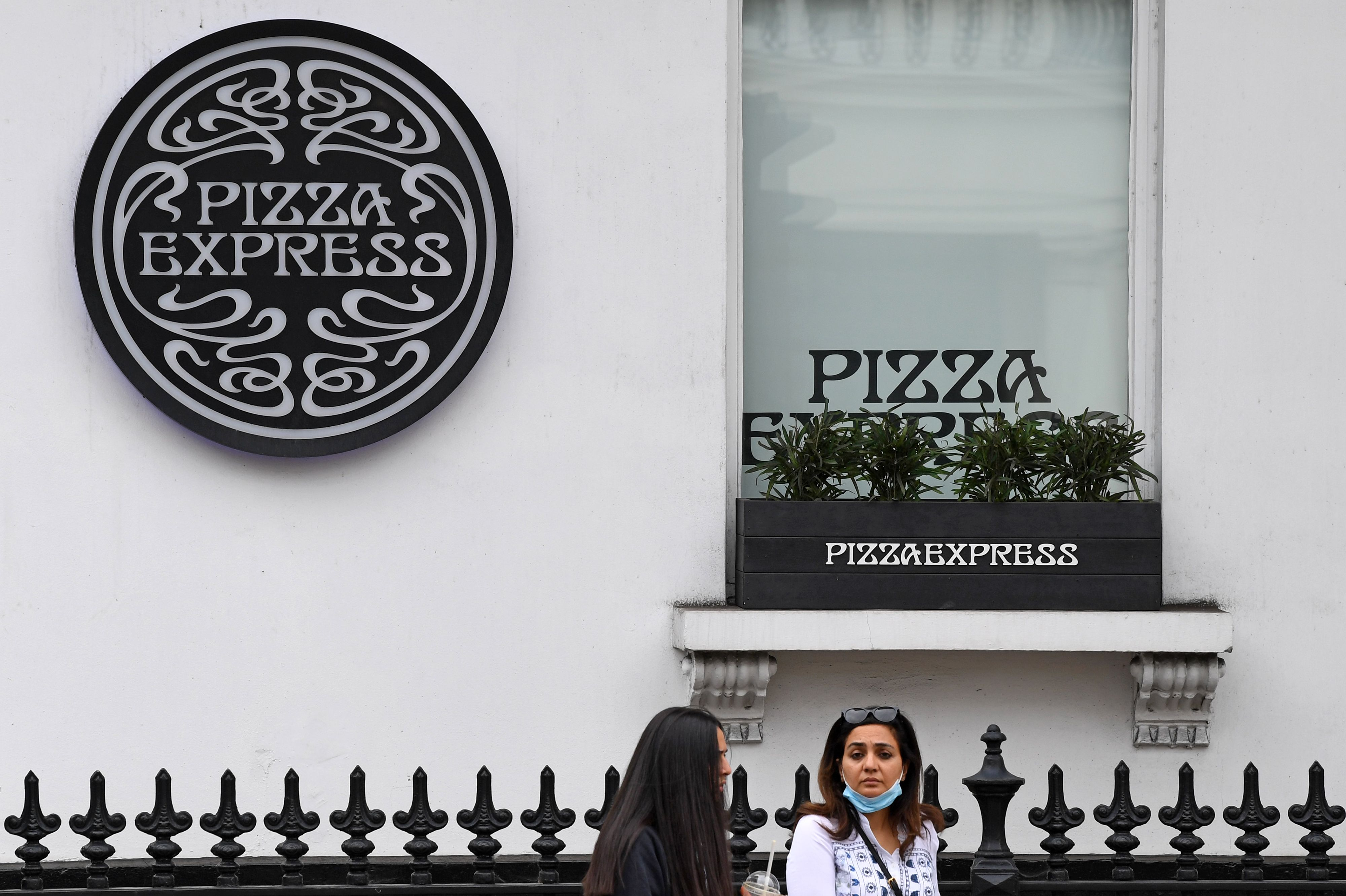 Pizza Express logo on the side of a Pizza Express restaurant in London