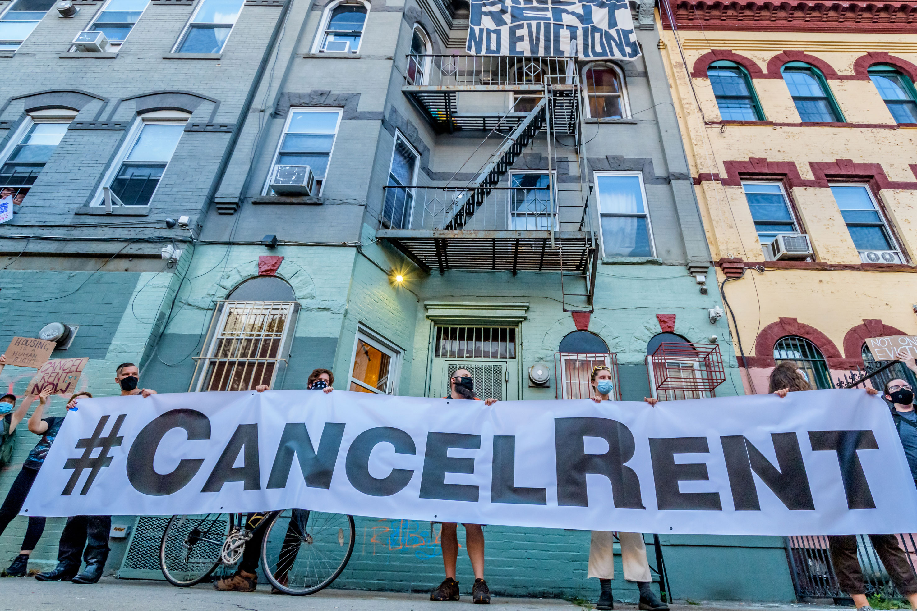 """Several protestors hold up a black and white banner printed with """"#CancelRent"""" in front of a blue apartment building in Bushwick."""