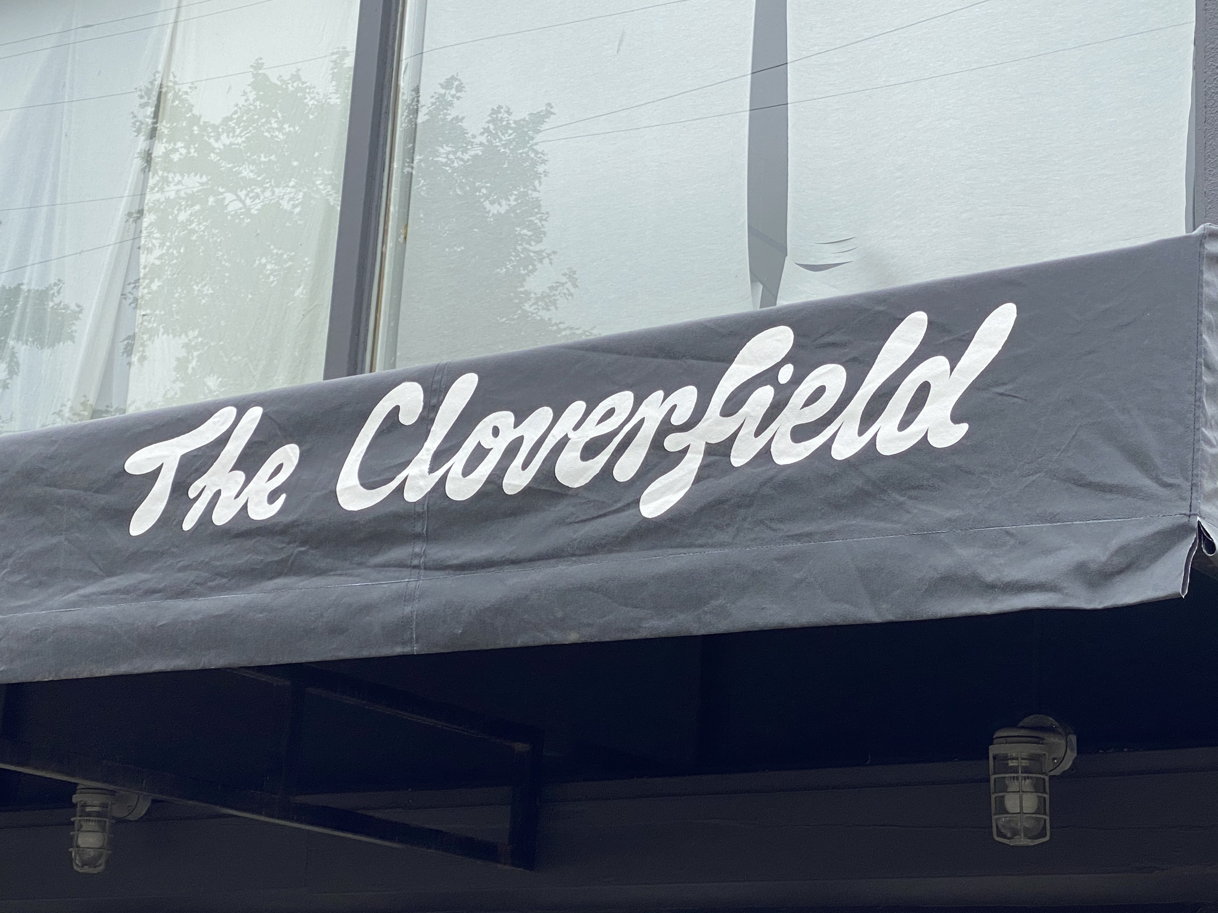 A black awning shows off language for a new restaurant called the Cloverfield.