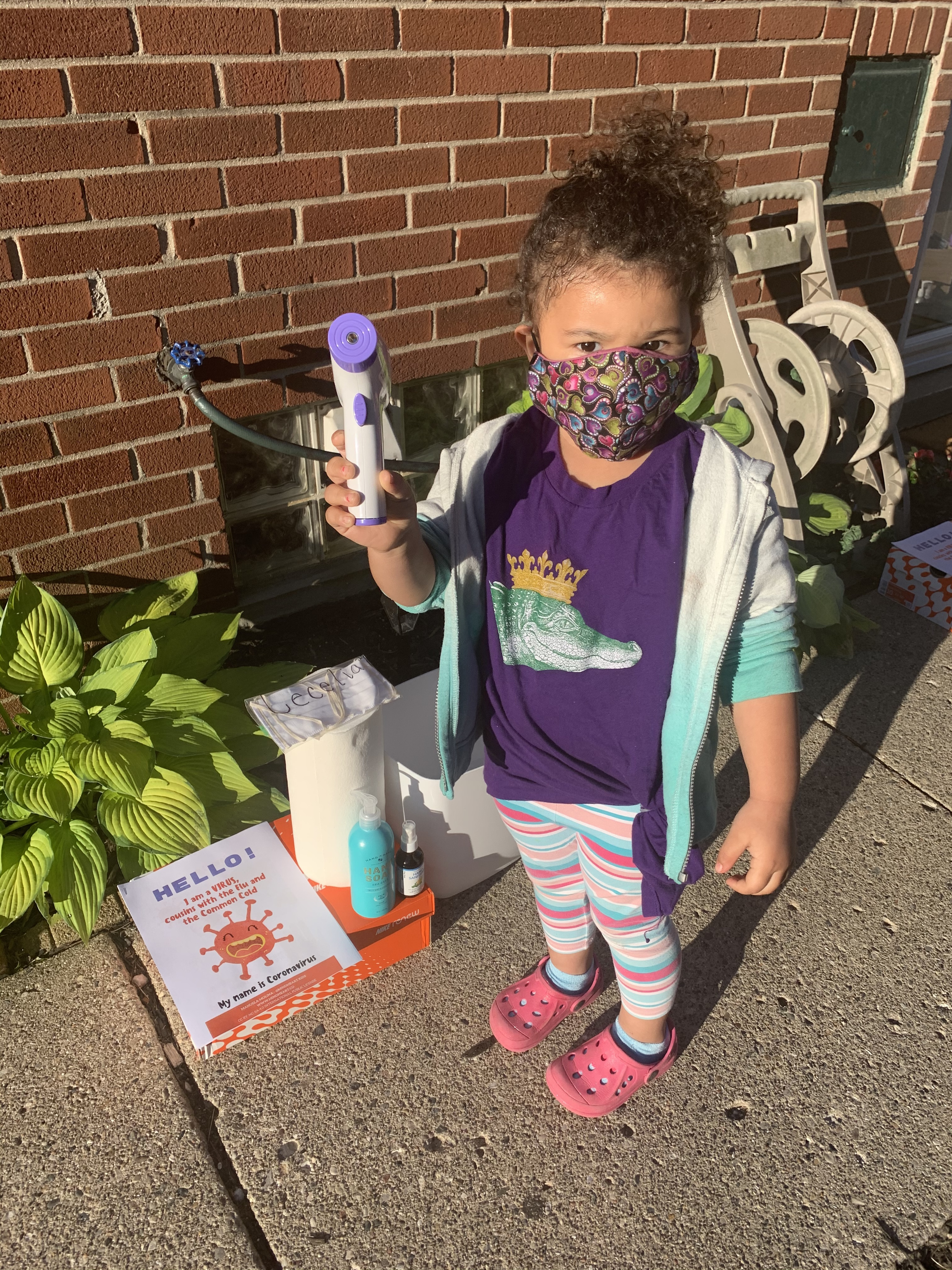 child in purple shirt stands with mask and thermometer outside of child care center in Detroit