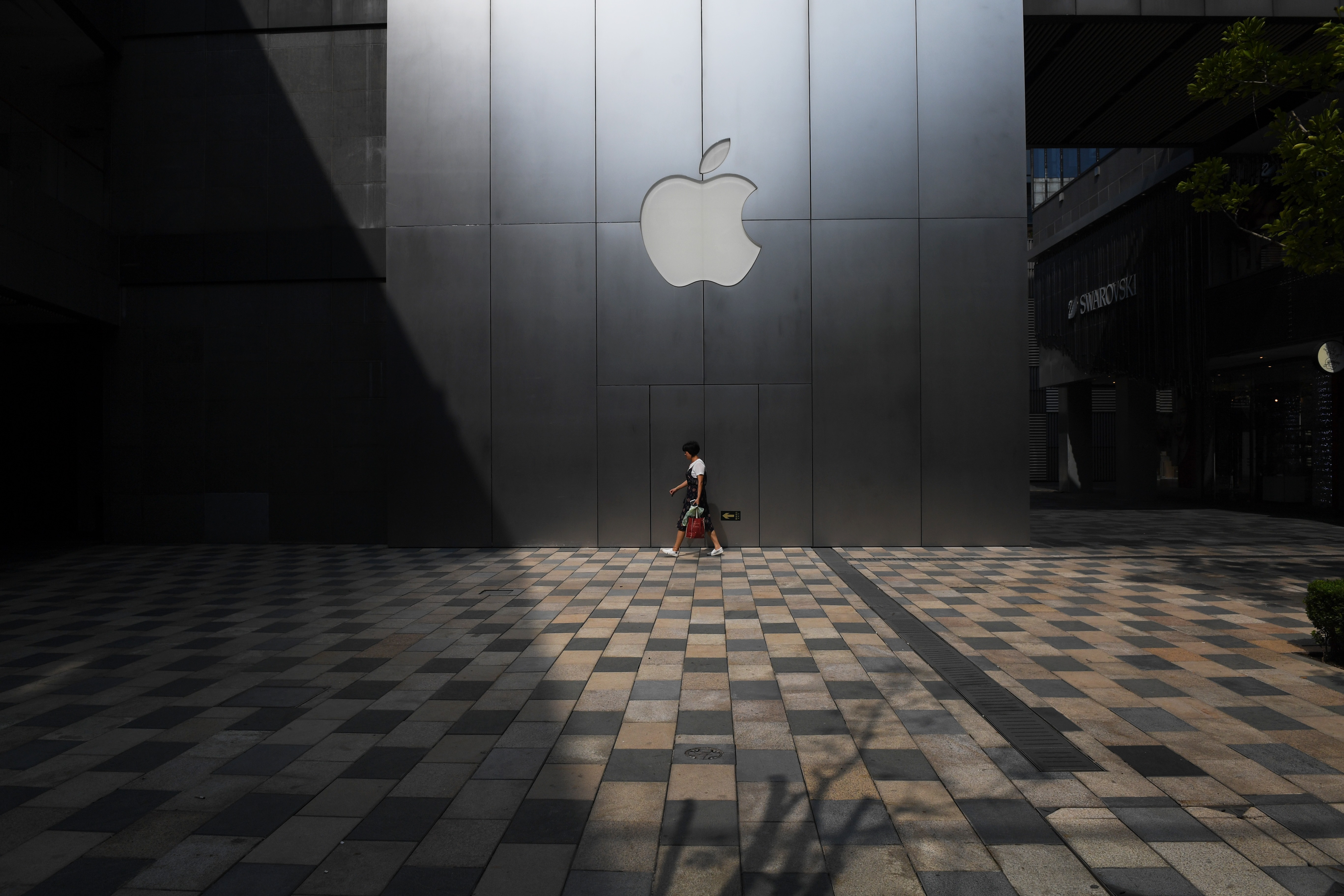 A person walks past an Apple store in Beijing, China.