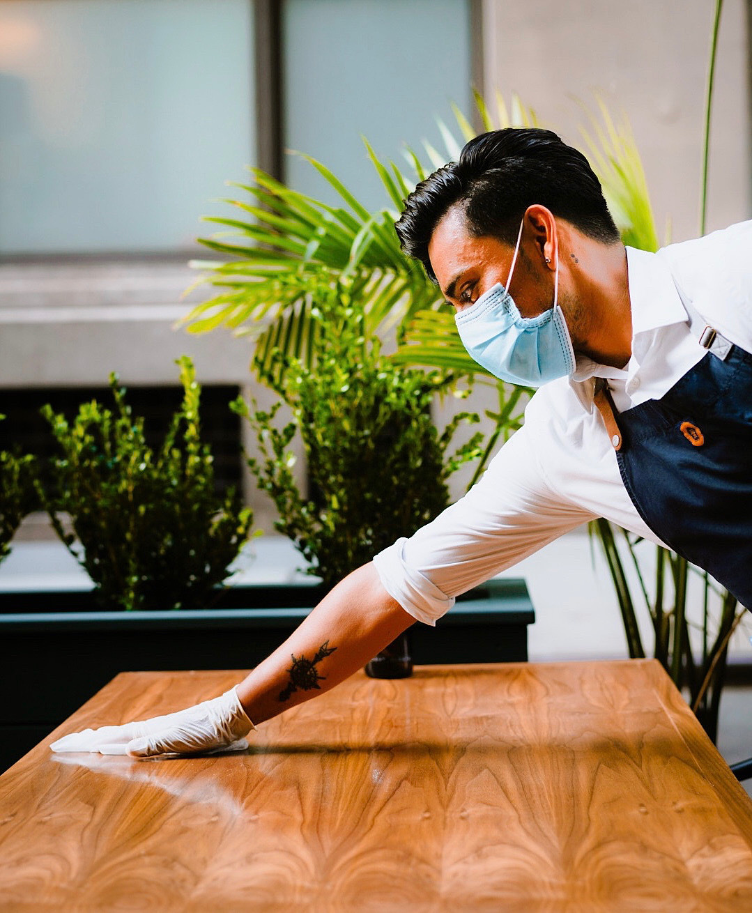 A man wearing a mask cleaning a wooden table