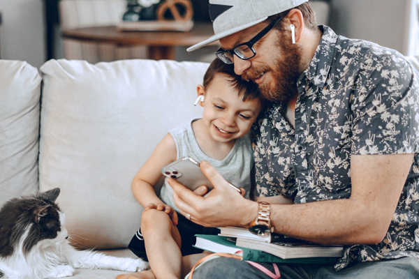 A father and child seated on a couch using the Duolingo app on his smartphone