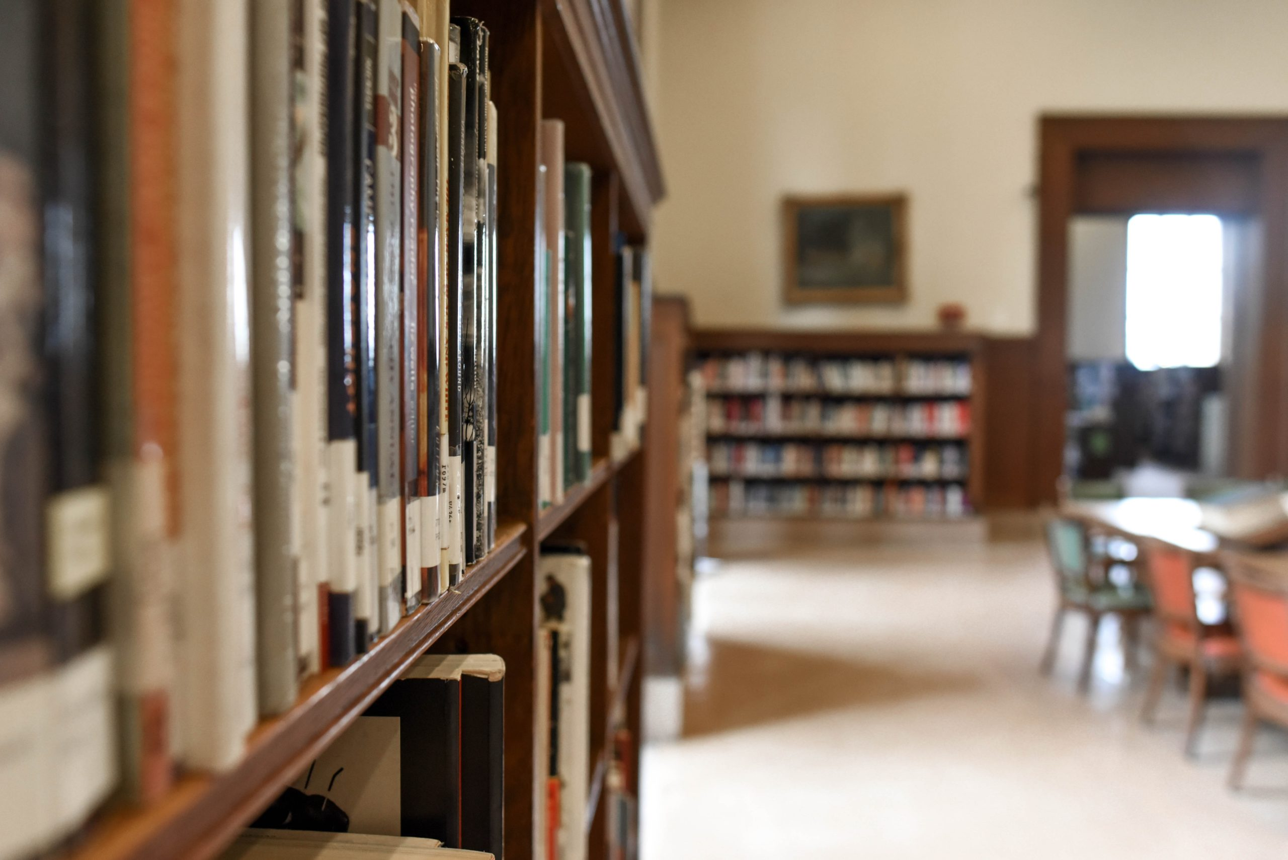 Shallow focus image of a shelf of books in an empty library.