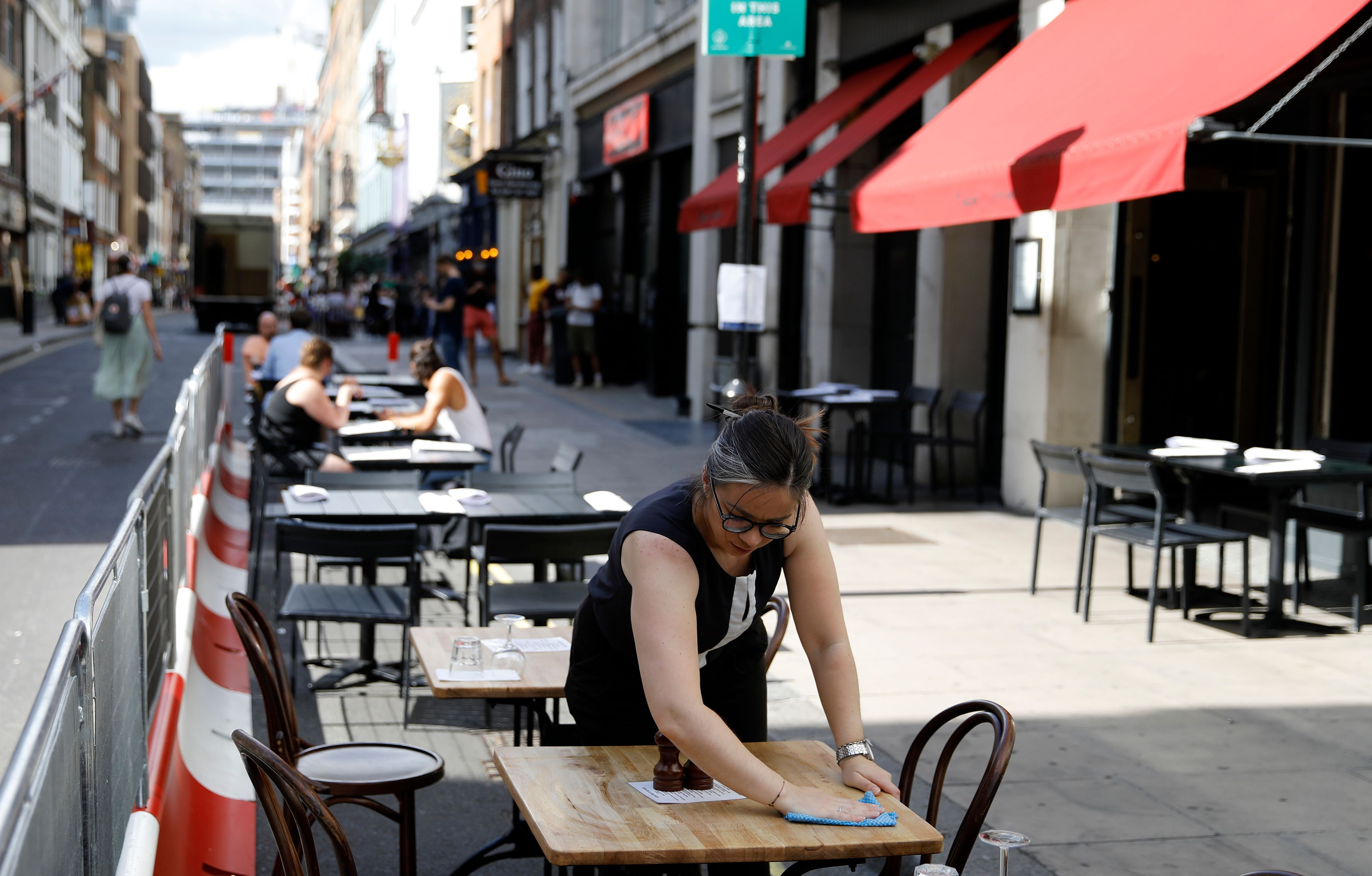 A restaurant worker cleans a table outside a London restaurant in the Eat Out to Help Out coronavirus discount scheme