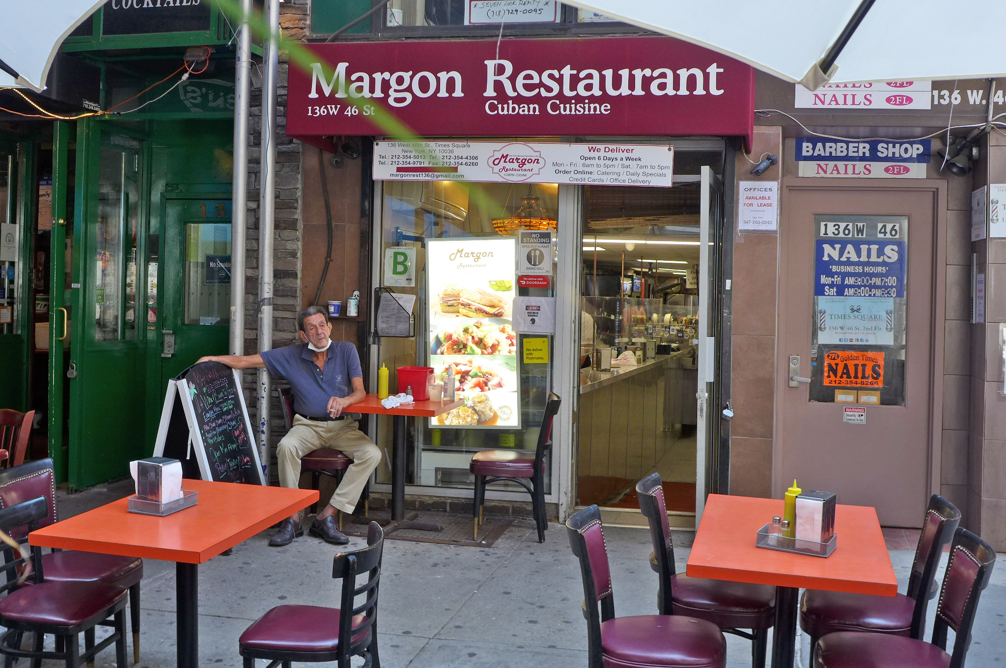 A small restaurant with a red awning and a man sitting out front at an orange table.