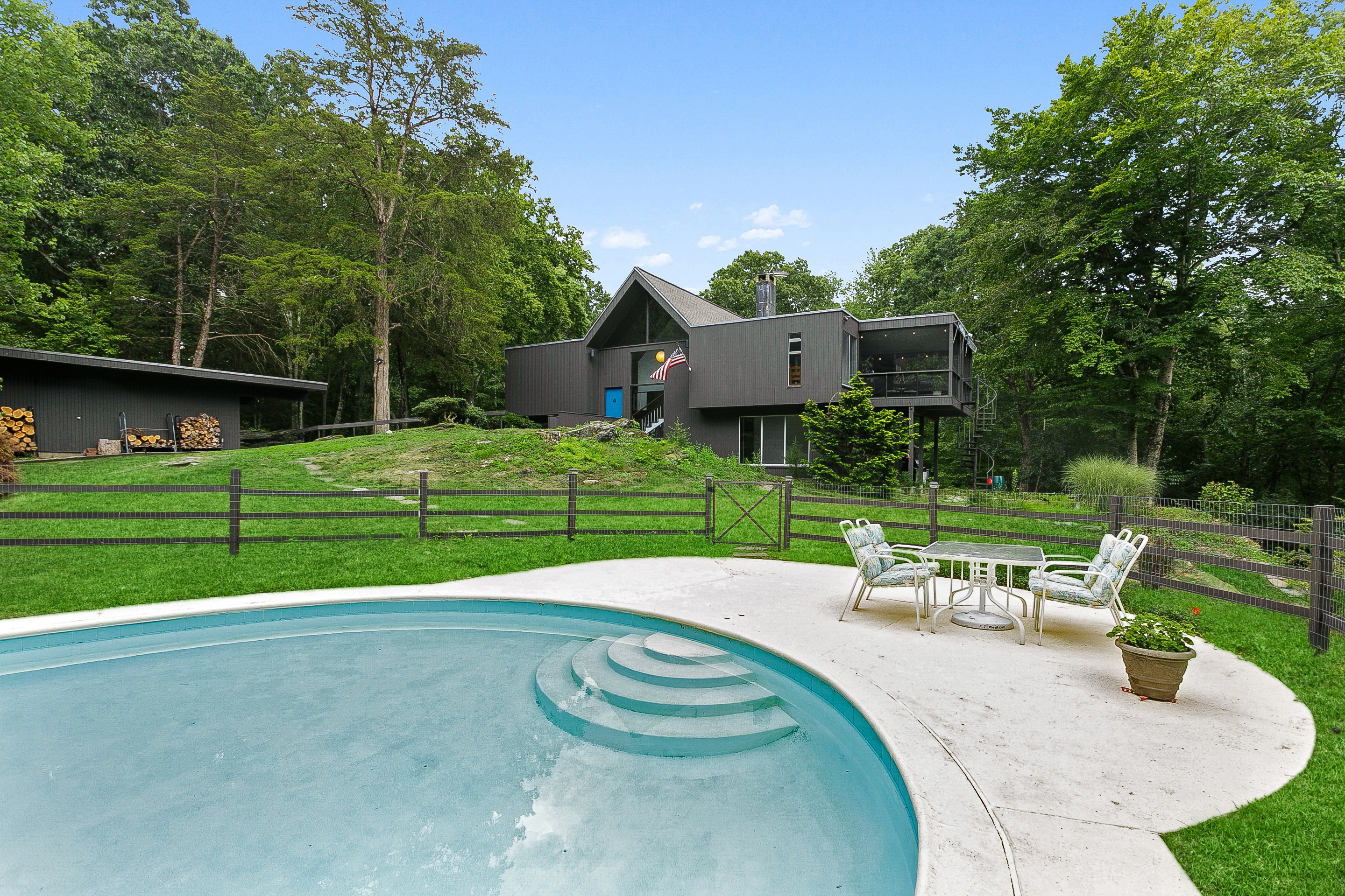 A swimming pool sits in the foreground of the photo with a gray midcentury style home and green grass in the back.