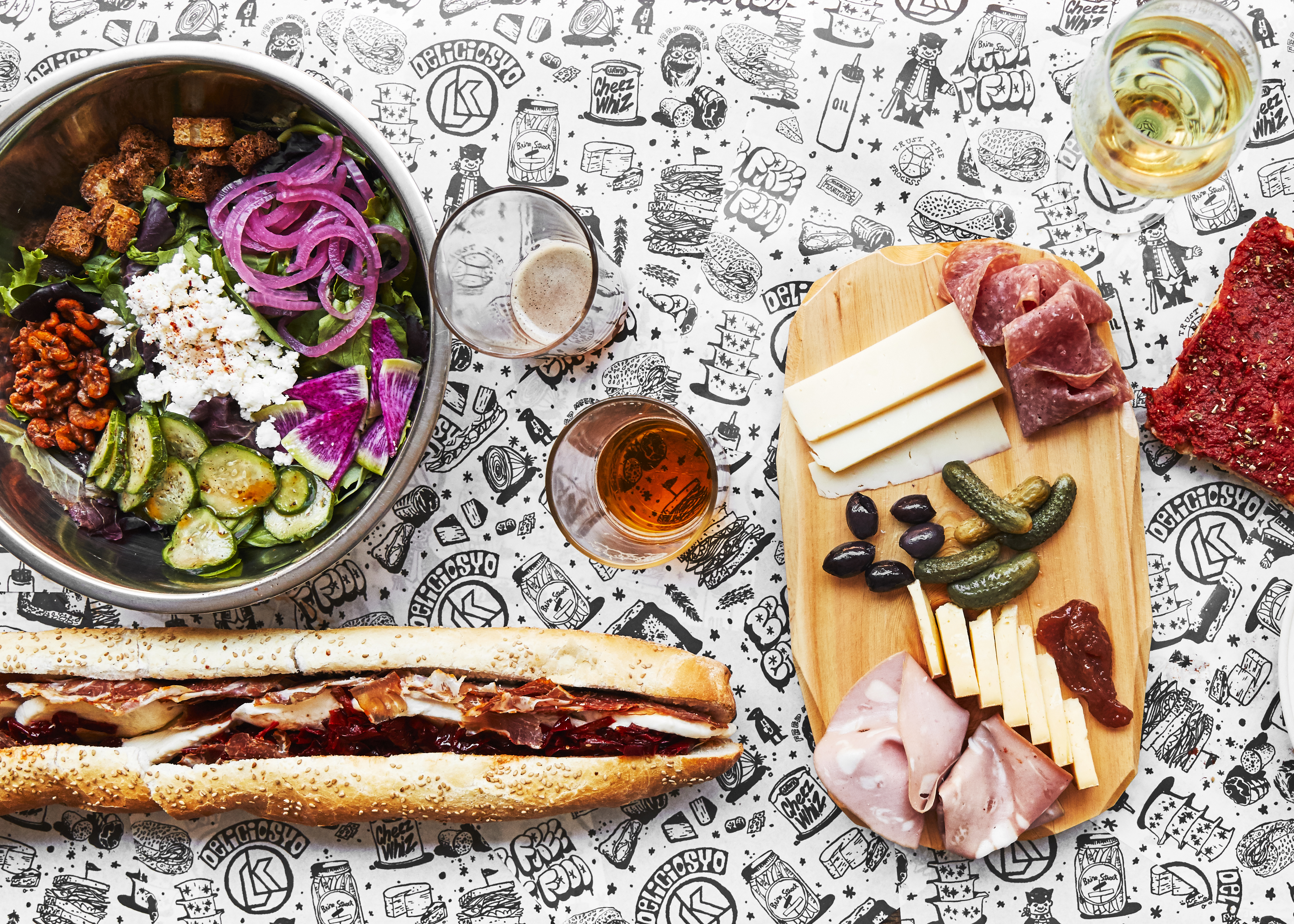 cheeseboard, salad, sandwich on long roll, and glasses of beer and wine on a black and white tablecloth decorated with food images