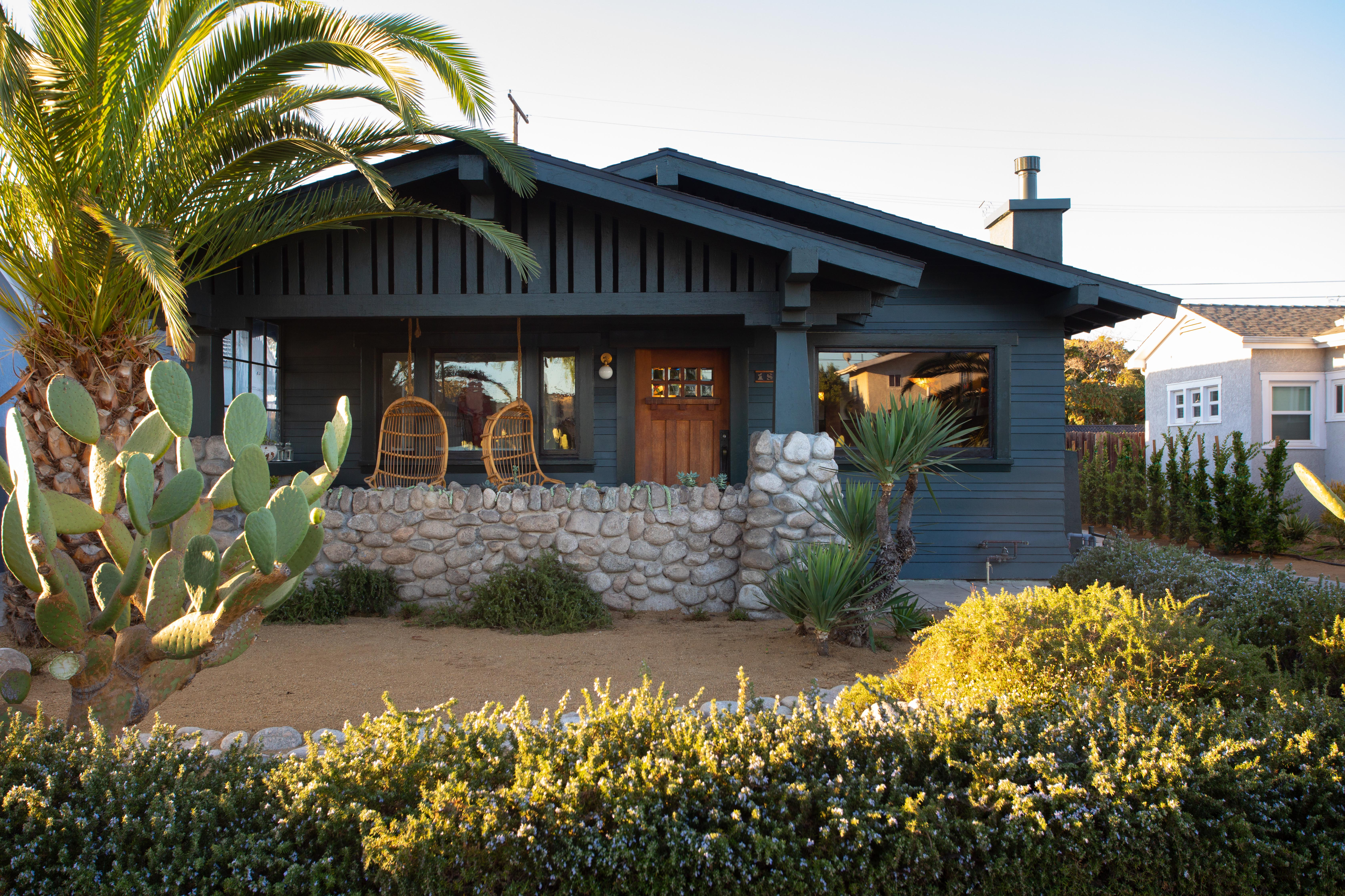 Dark gray-blue house with twin roofs surrounded by plants.