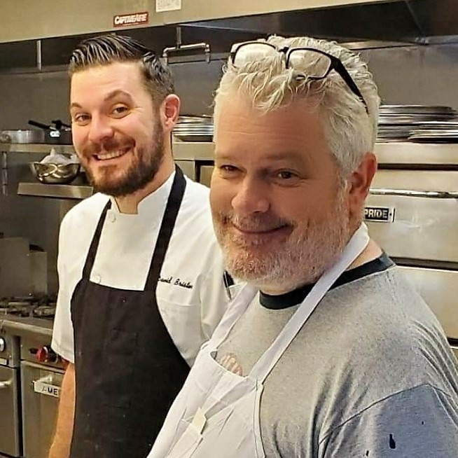 Two chefs stand in a kitchen