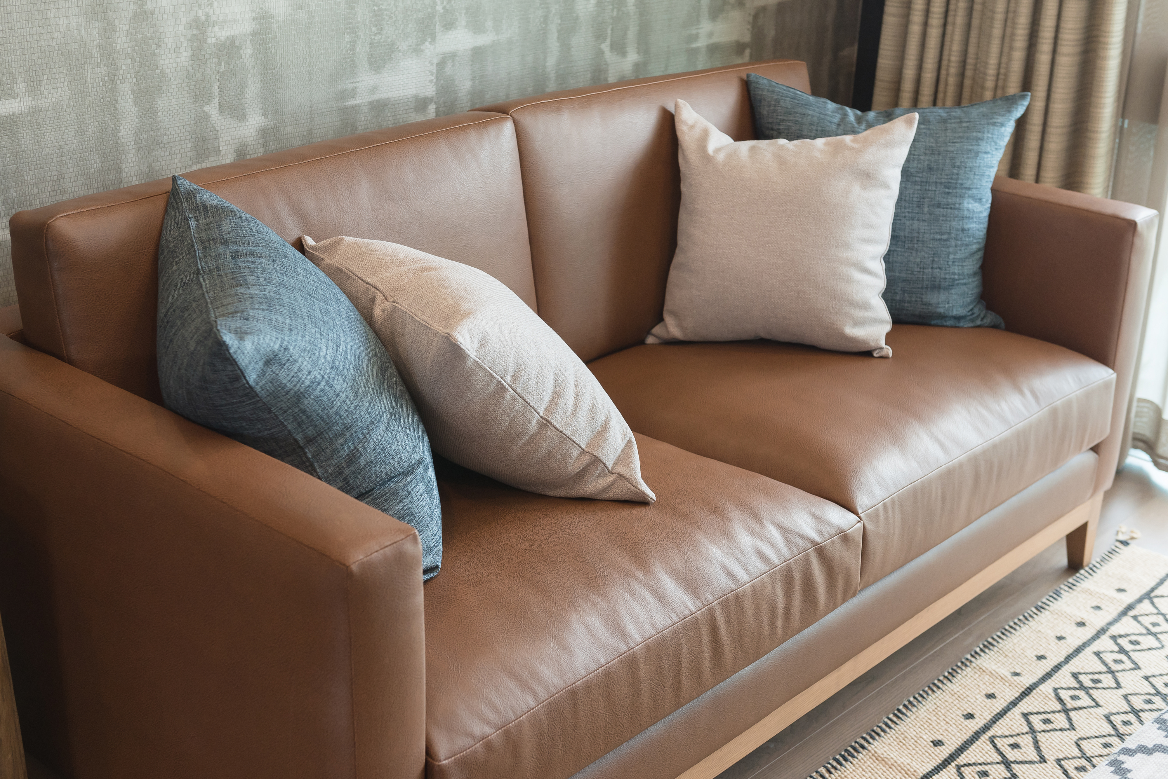 Brown leather couch with pillows