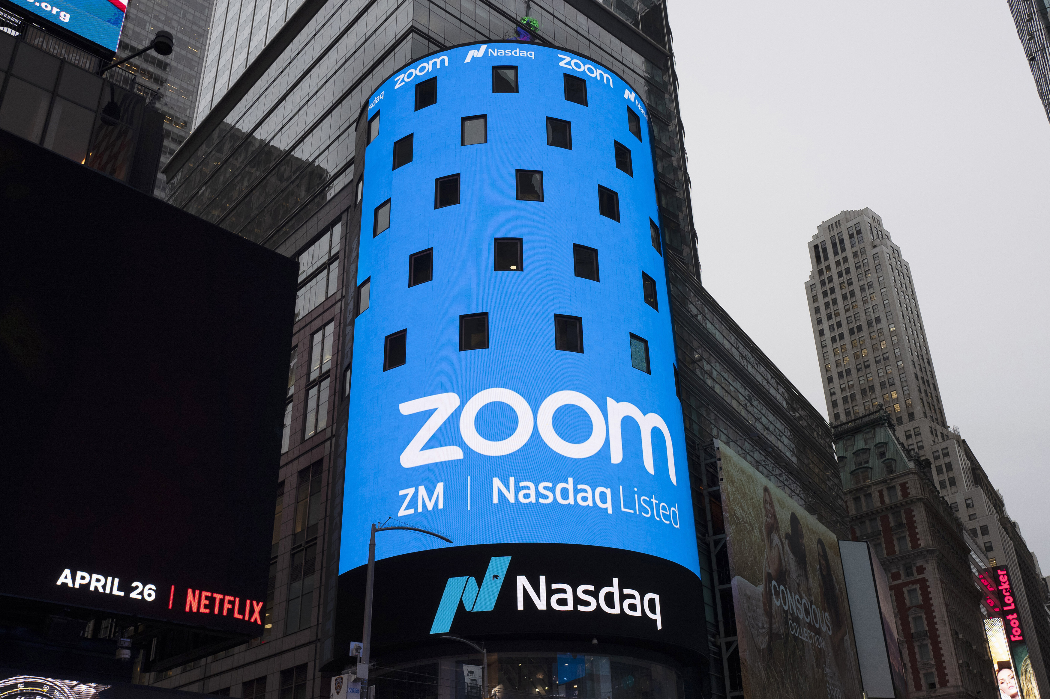 FILE - This April 18, 2019, file photo shows a sign for Zoom Video Communications ahead of the company's Nasdaq IPO in New York. Now that Zoom has emerged as one of the most popular ways to get together virtually while the coronavirus pandemic keeps people apart, the company is trying to build a more secure fortress around the billions of conversations occurring on its videoconferencing service daily. (AP Photo/Mark Lennihan, File) ORG XMIT: NYSB221