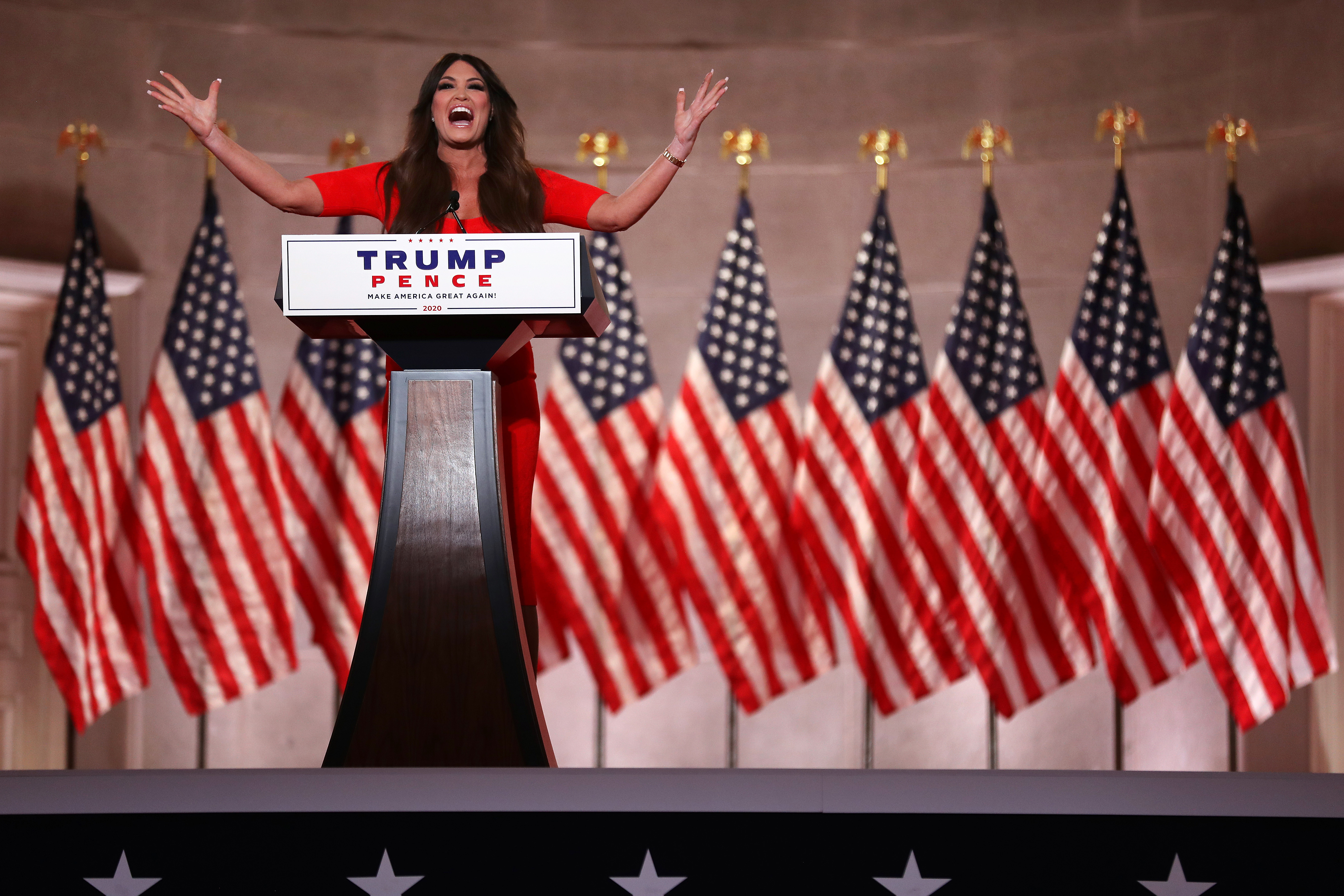 Standing behind a podium and in front of a long row of American flags, Kimberly Guilfoyle pre-records her address to the Republican National Convention at the Mellon Auditorium on August 24, 2020 in Washington, DC.