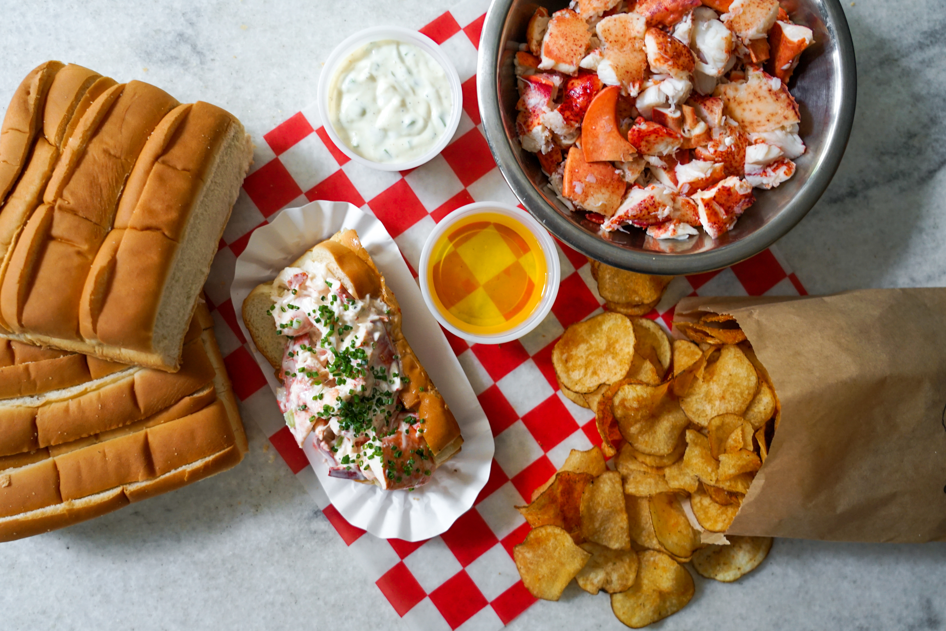 lobster roll, bowl of lobster chunks, potato chips in brown paper bag, and bread rolls on a red and white checked placemat