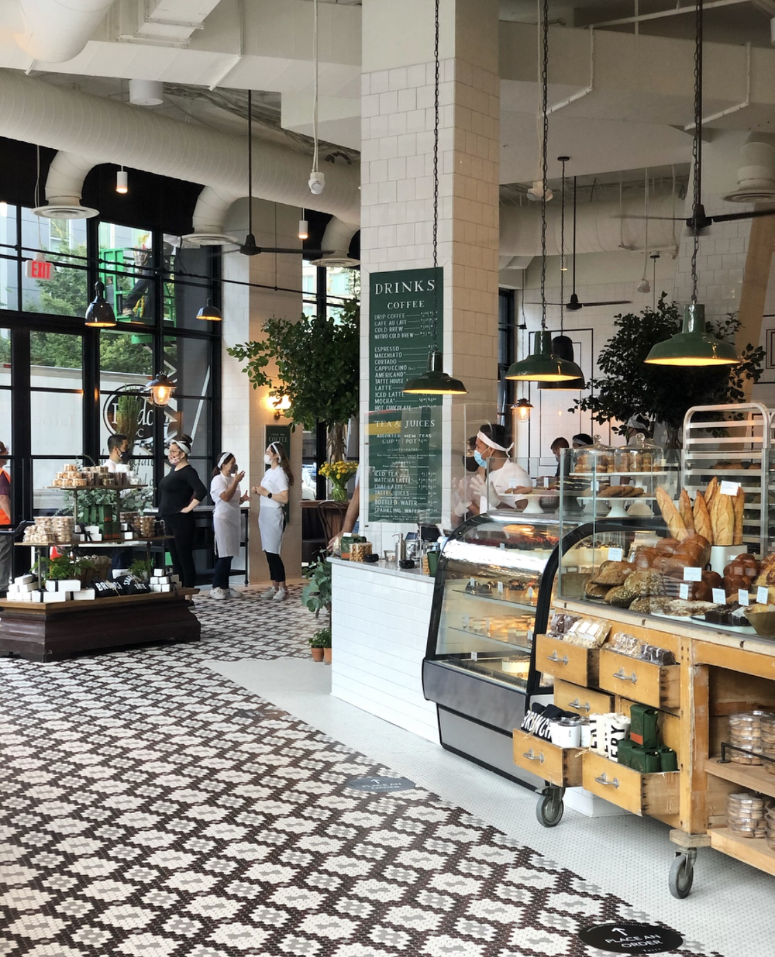 The interior of a bakery with black-and-white floors, high ceilings, and pastry cases. Workers stand in the background chatting in face masks.