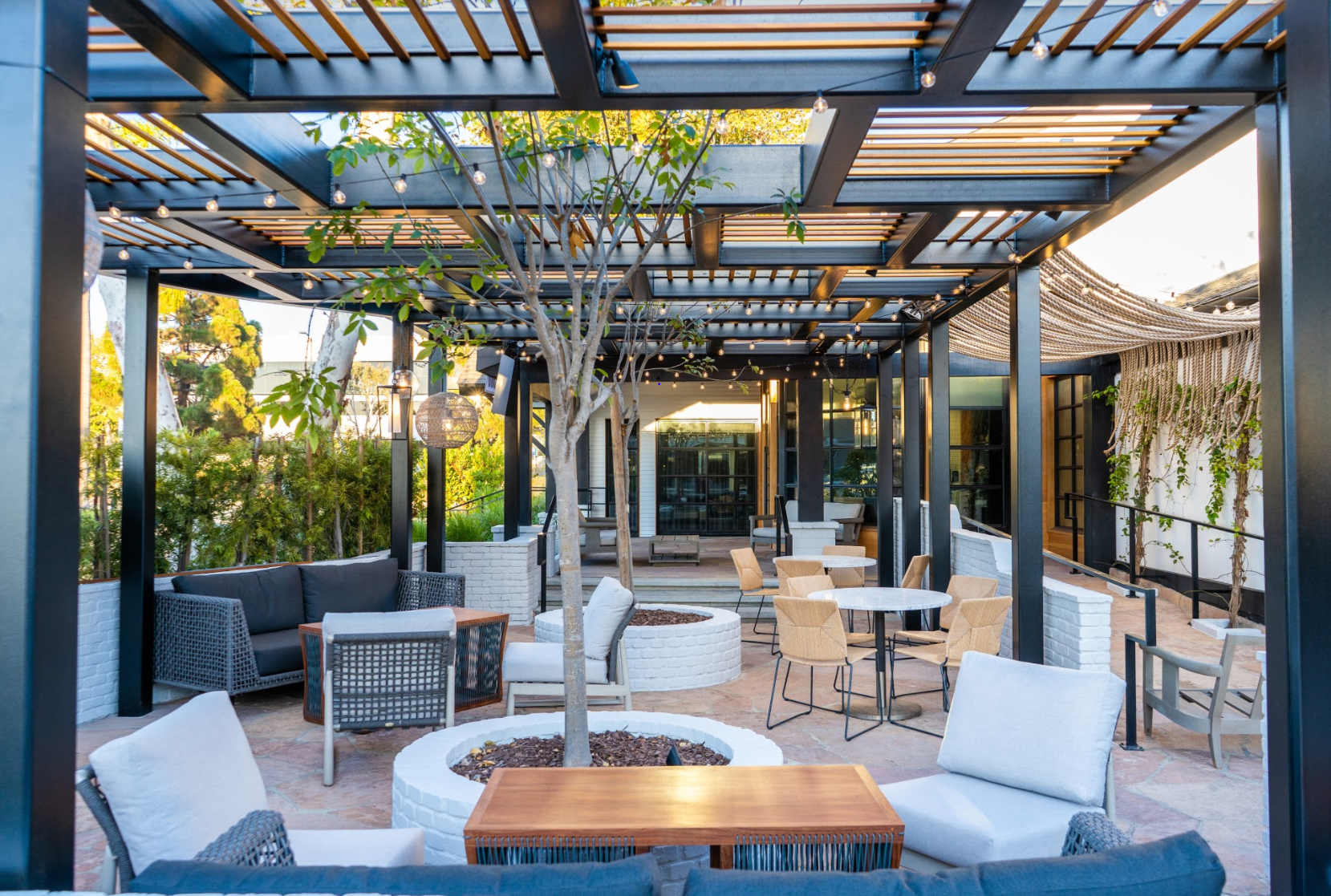 Outdoor patio with white chairs and decorative accents and trellice covering at Jerry's Patio and Bar in Marina del Rey.