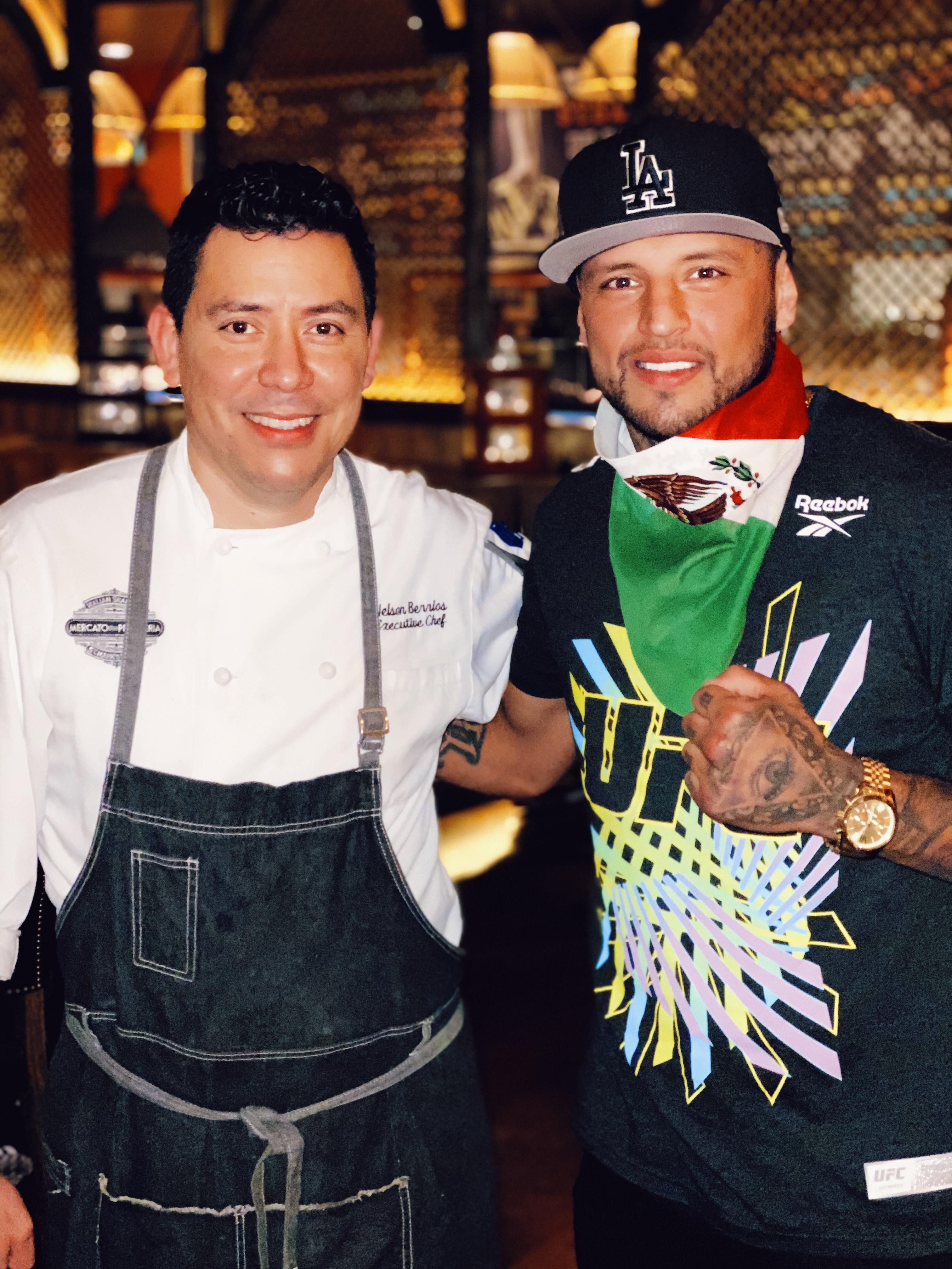 A chef in a white jacket stands next to a man with a Mexican flag scarf around his neck