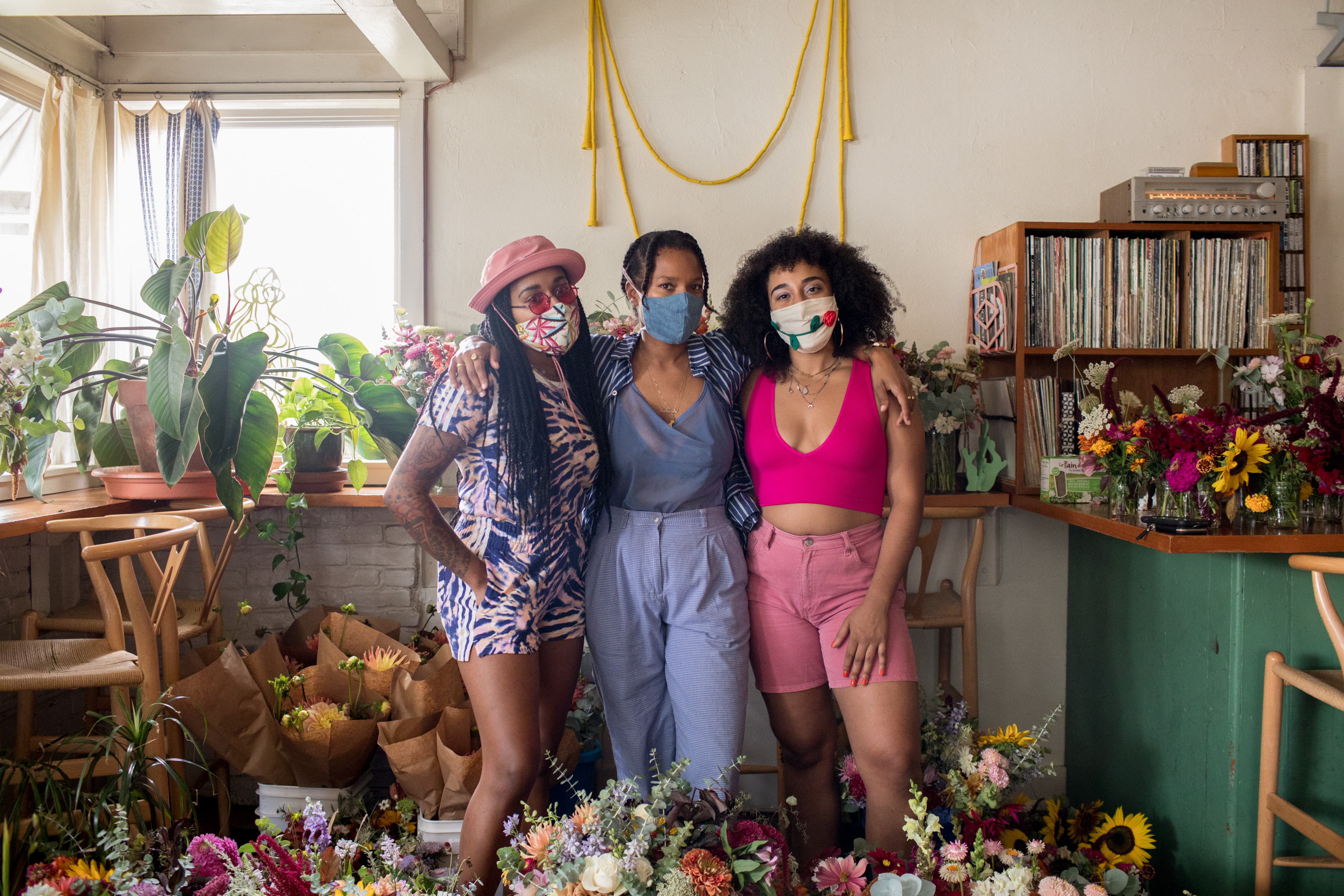 Two women, wearing masks, look ahead at the camera surrounded by flowers all over the floor and nearby counter.